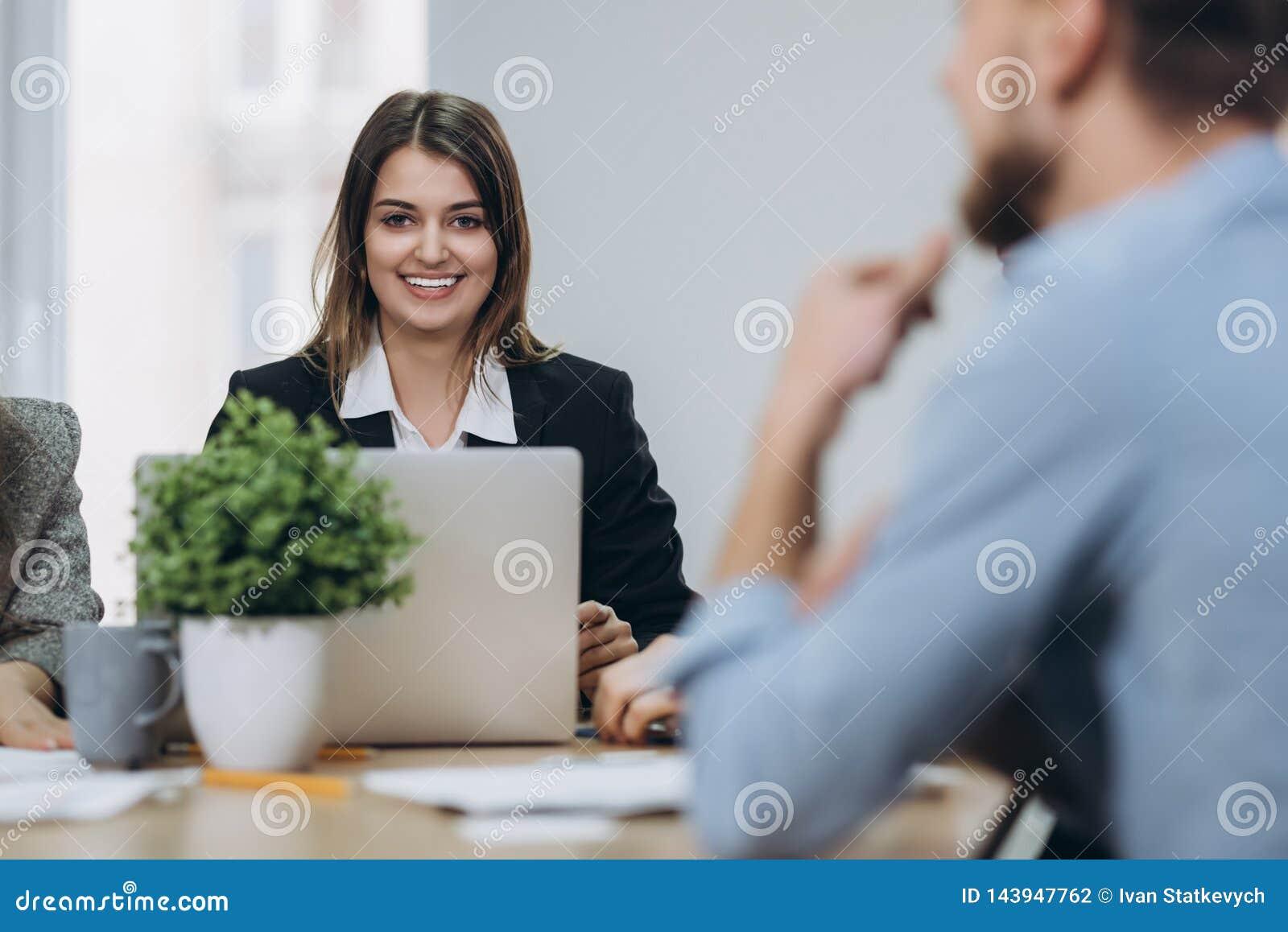 Geschoten van een aantrekkelijke rijpe onderneemster die aan laptop in haar werkstation werken