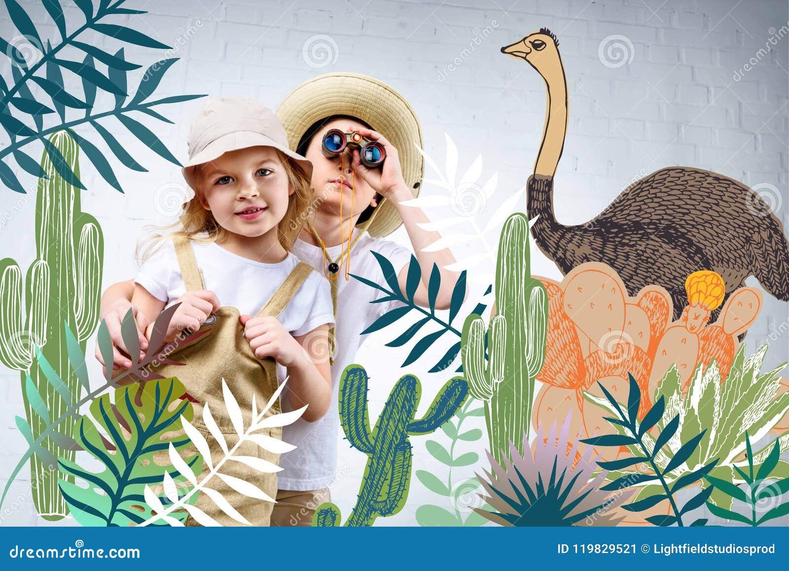 Geschwister in der Safari kostümieren das Umarmen und das Betrachten in den Ferngläsern Kakteen