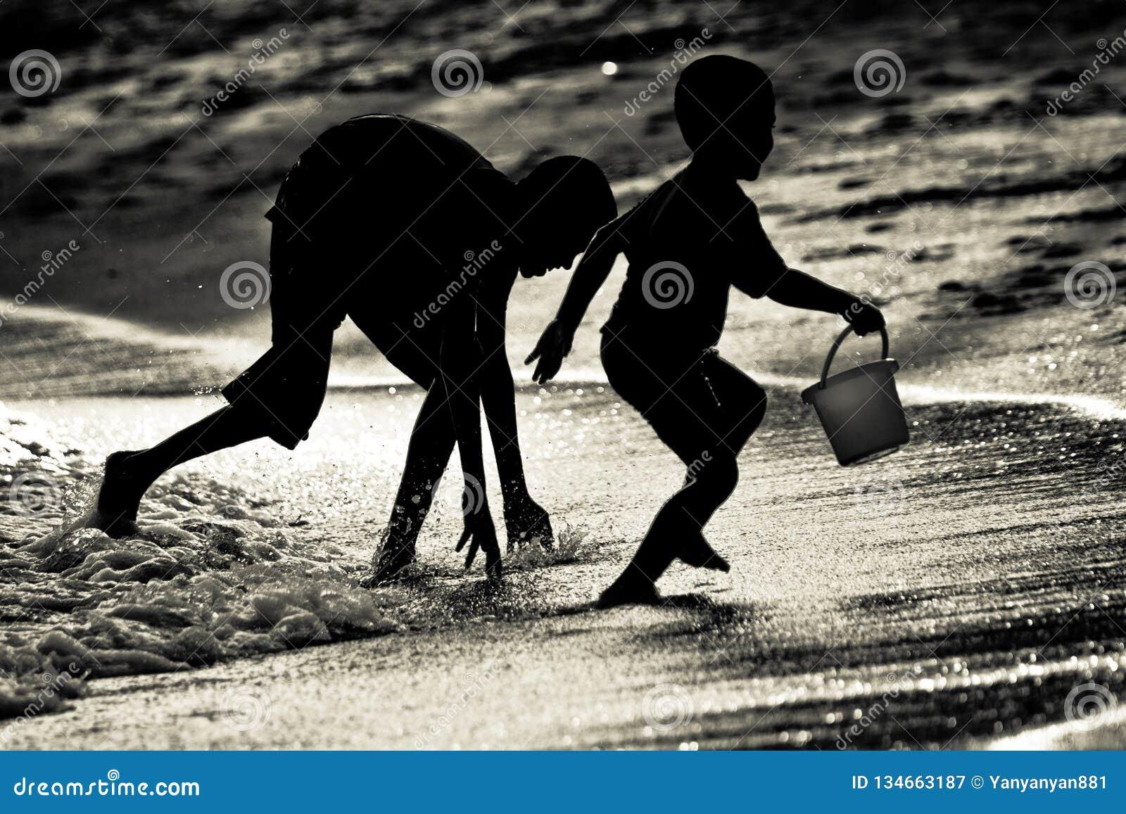 Geschwisterbrüder, die das Fangen an einem Strand in Singapur spielen