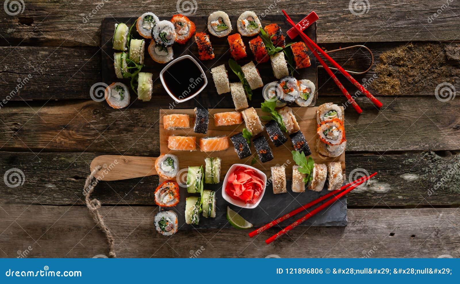 Gesetztes Lebensmittelfoto der Sushi Rolls diente auf brauner hölzerner und Schieferplatte Hohe und Draufsicht des Abschlusses vo