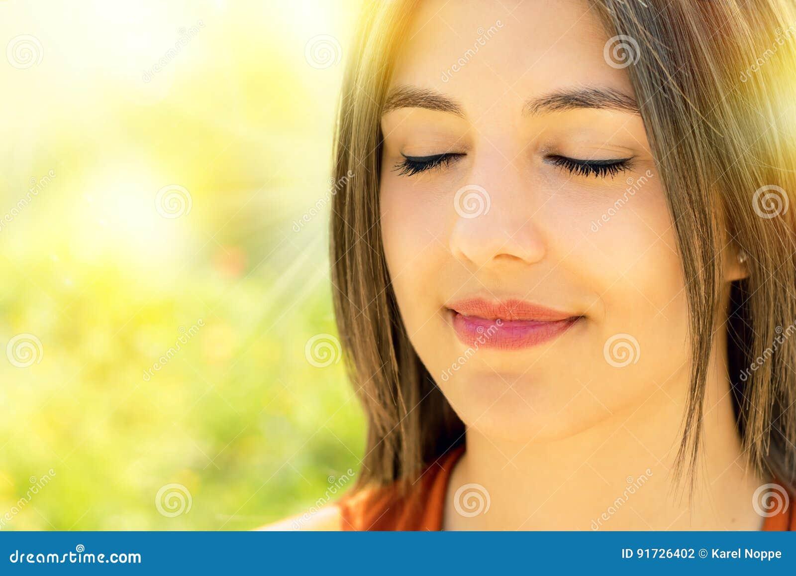 Gesicht geschossen von der entspannten Frau, die draußen meditiert