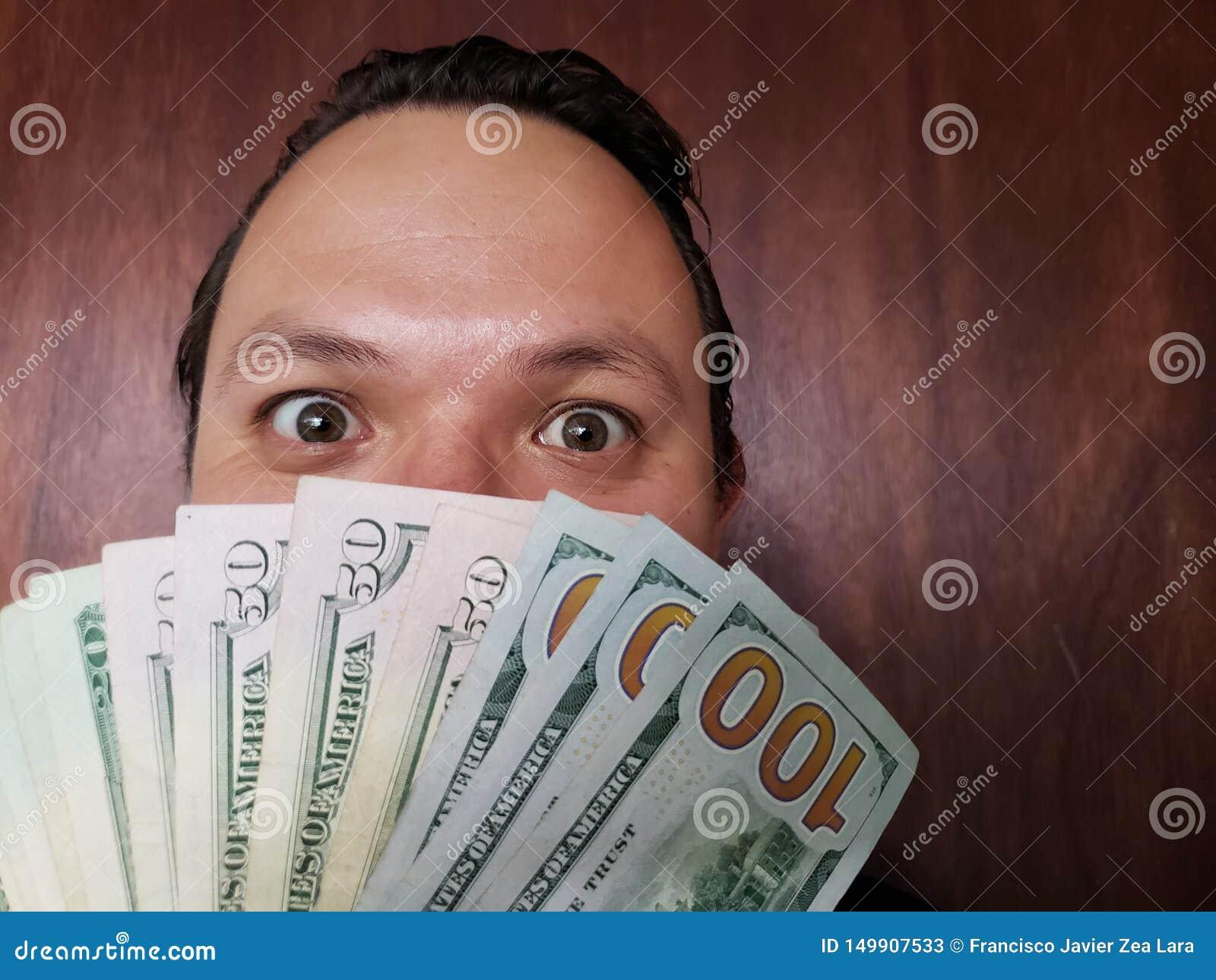 Gesicht mit Gefühlausdruck eines jungen Mannes und der amerikanischen Banknoten
