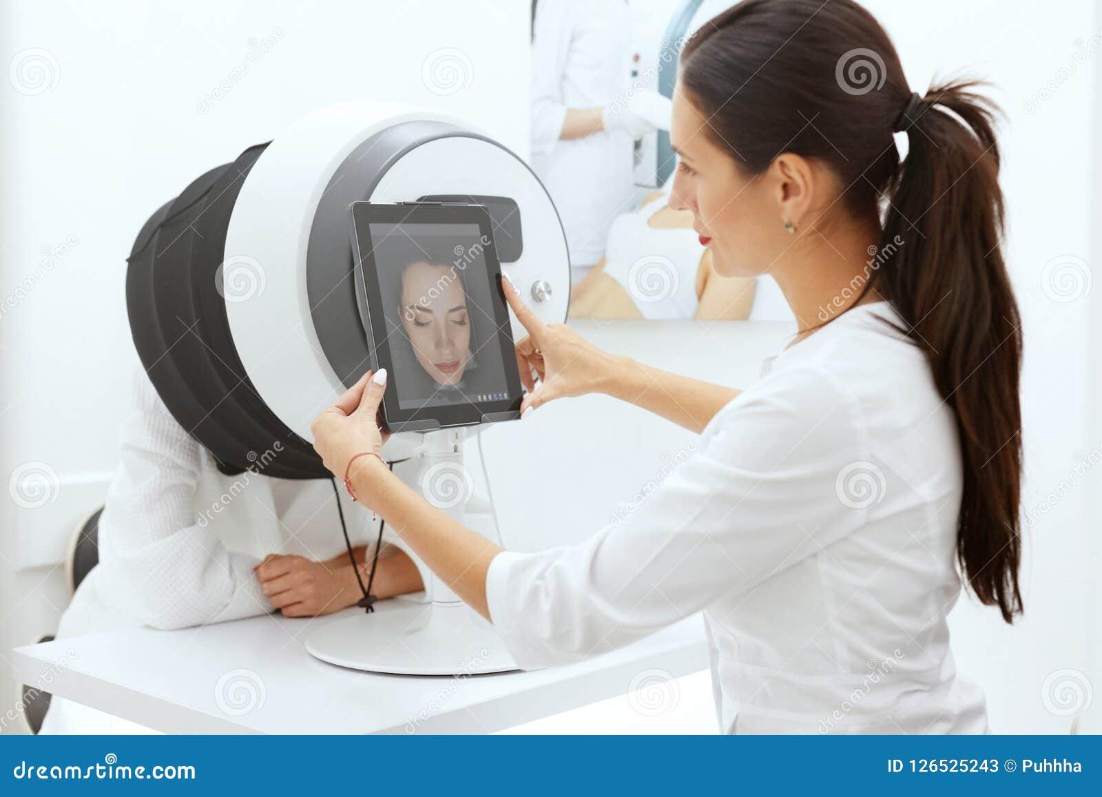 Gesichts-Haut-Analyse Frau am Cosmetology, der Haut-Diagnose tut