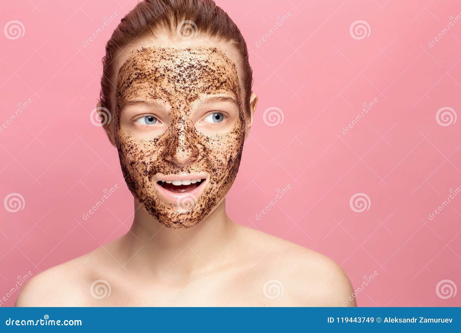 Gesichts-Haut scheuern sich Porträt sexy lächelnder weiblicher vorbildlicher Applying Natural Coffee-Maske, Gesicht scheuern sich