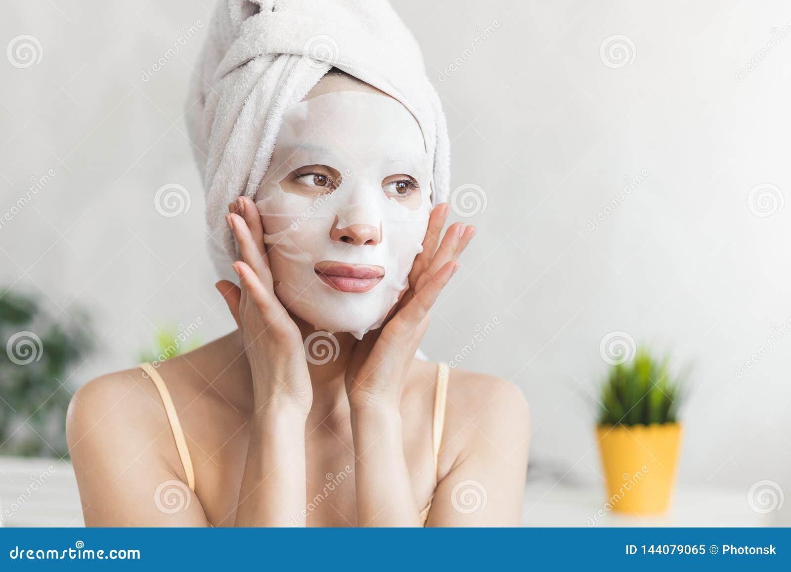 Gesichtshautpflege Attraktive junge Frau eingewickelt im Bad-Tuch, mit weißer befeuchtender Gesichtsmaske Nahaufnahmeportrait get