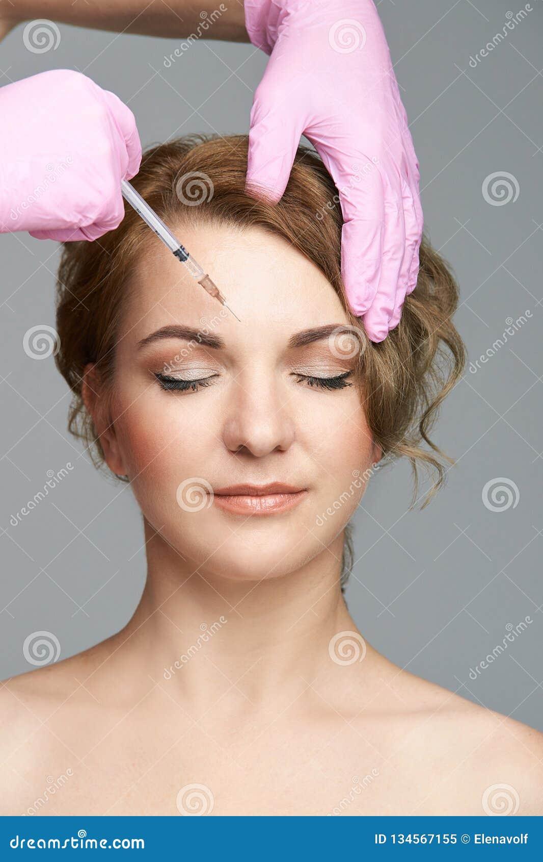 Gesichtsnadeleinspritzung Verfahren junge Frau Cosmetology Doktorhandschuhe