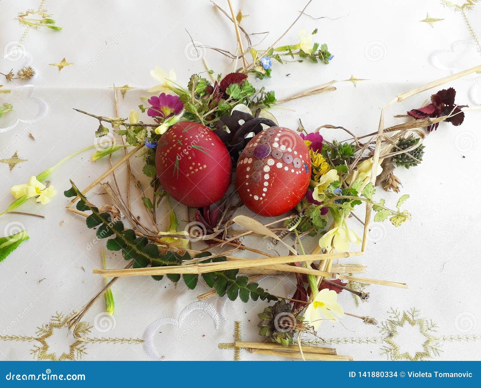 Gesierd rood paasei met verse wilde bloemen en kruiden