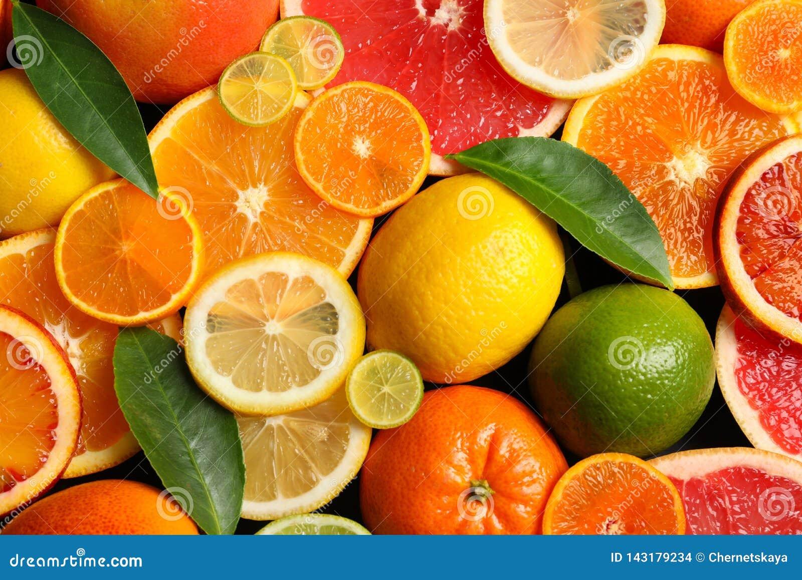 Gesneden en gehele citrusvruchten met bladeren als achtergrond