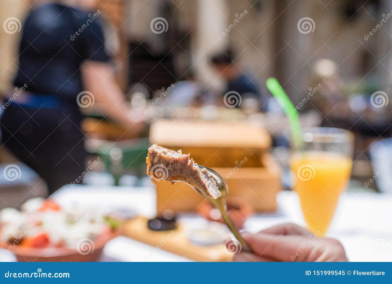 Gesneden geroosterde lamskoteletten op een vork De vrouw heeft een diner in een Griekse herberg