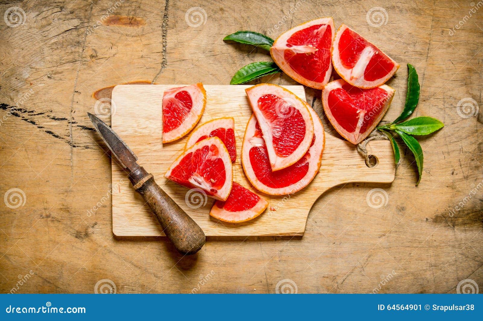 Gesneden grapefruit op een houten Raad met bladeren