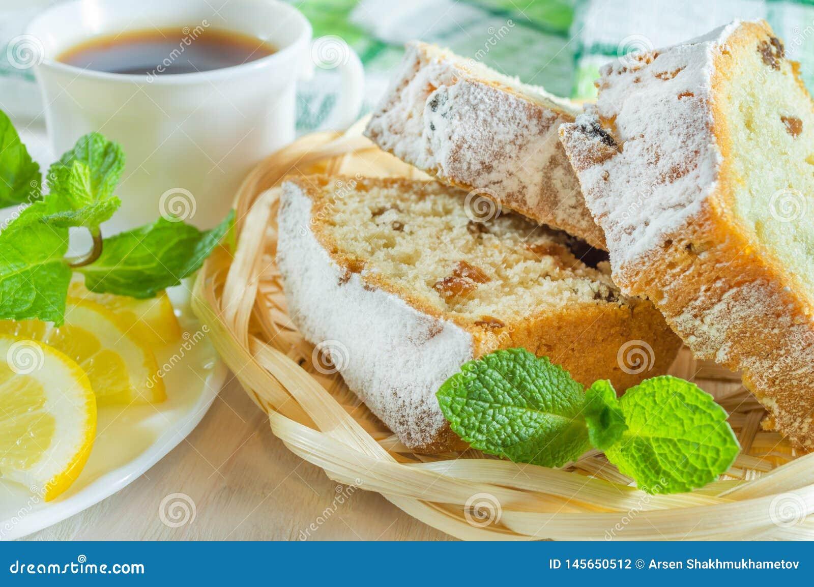 Gesneden koekjescake, een kop thee, citroenplakken en muntbladeren Heerlijk ontbijt of dessert
