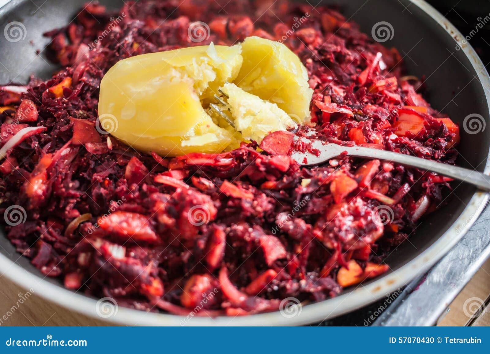 Gesneden wortel, rode biet en ui met gekookte aardappel op bovenkant