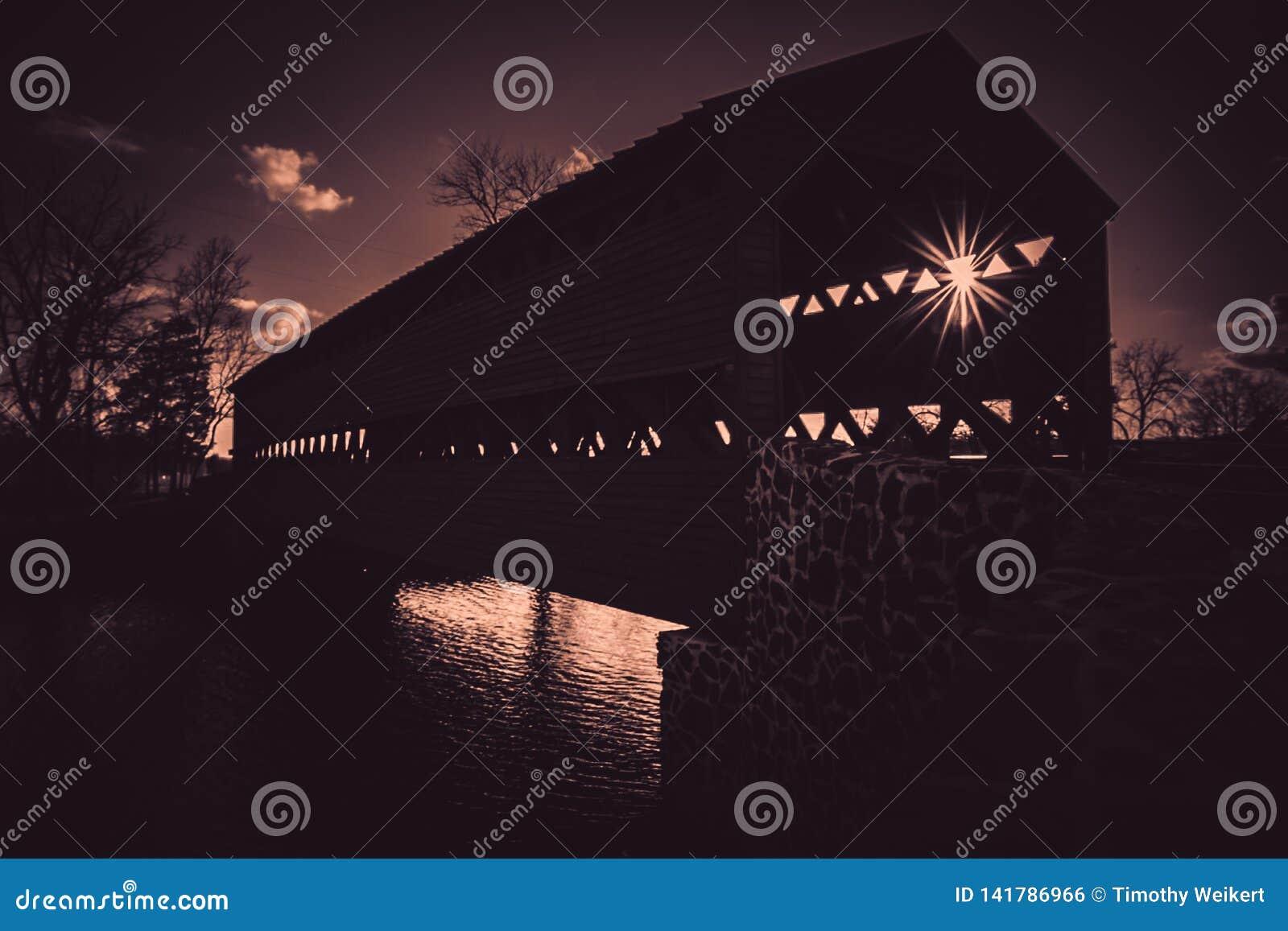 Gespenstische Sachs-überdachte Brücke in Gettysburg, PA im Schattenbild mit einem Sonnendurchbruch