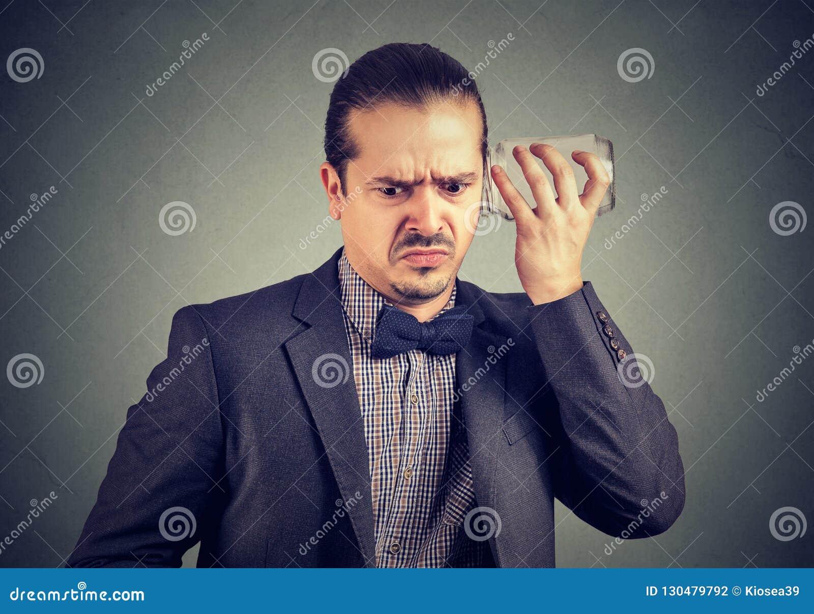 Gestörter Mann, der mit Glasgefäß heimlich zuhört