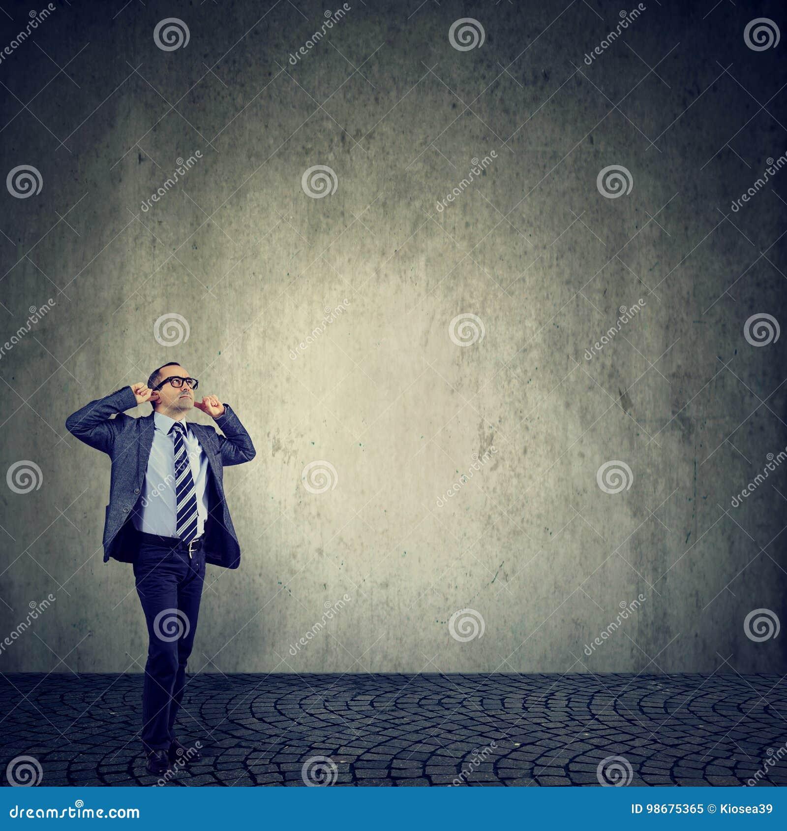 Gestörter Mann, der Ohren mit den Fingern frustriert mit lauten Geräuschen verstopft