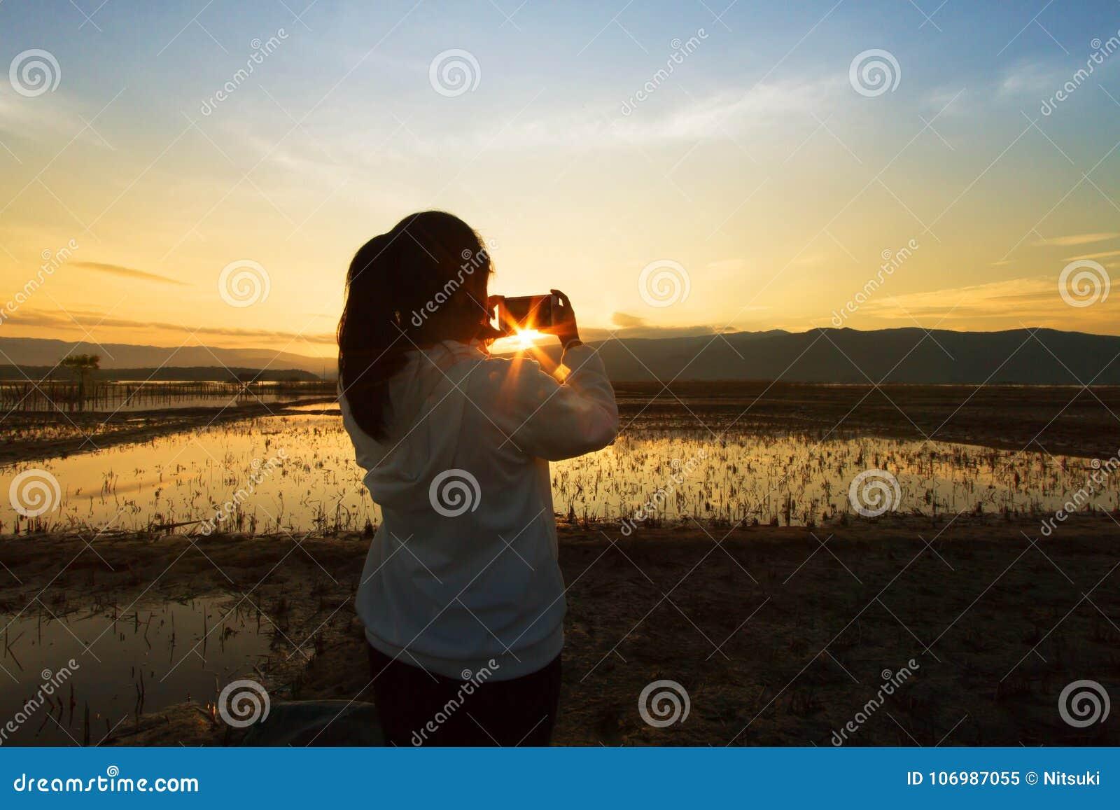Gestalten Sie Naturszene von den Frauen landschaftlich, die das Foto auf drastischen Himmel schießen
