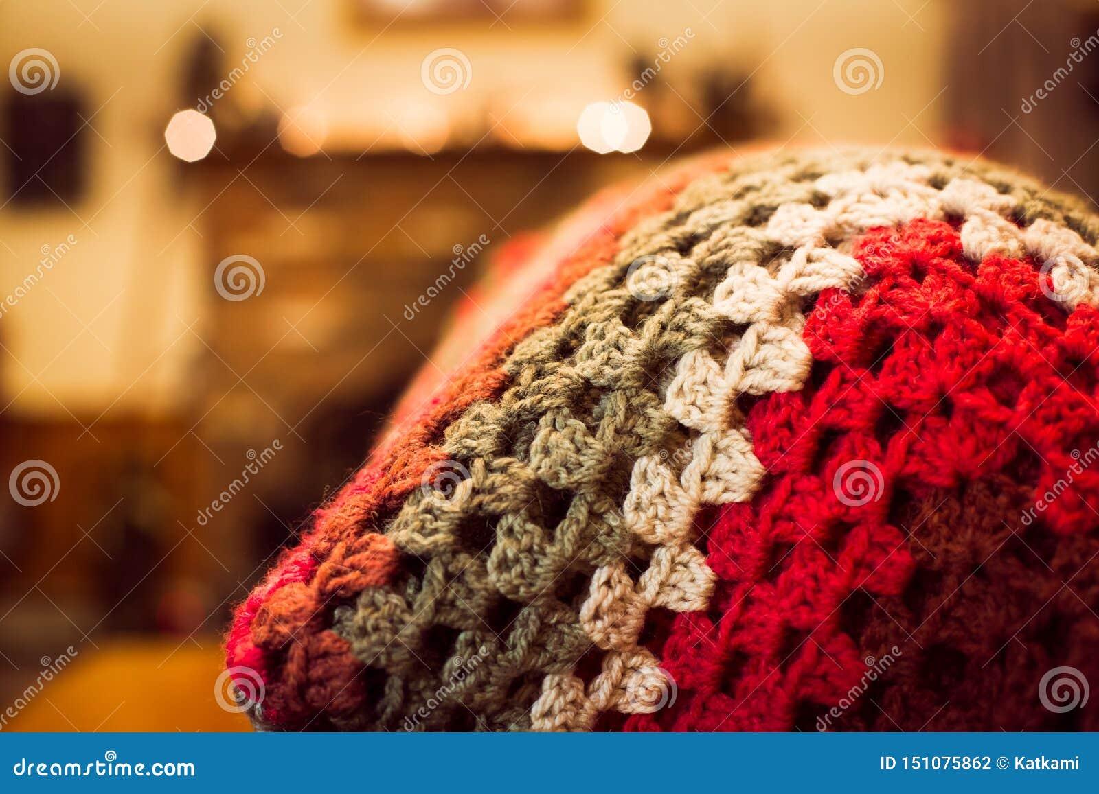 Gestemd rood haakt deken op de rug van een bank in een familieruimte