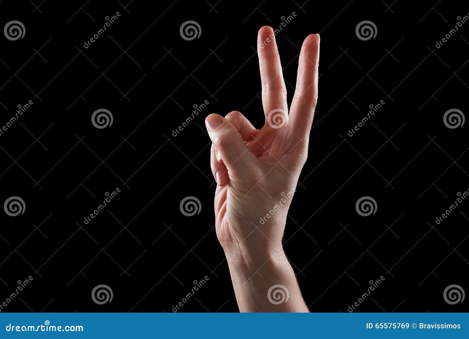 Gesticule, a mão da jovem mulher indica os dispositivos do sentido ou do toque