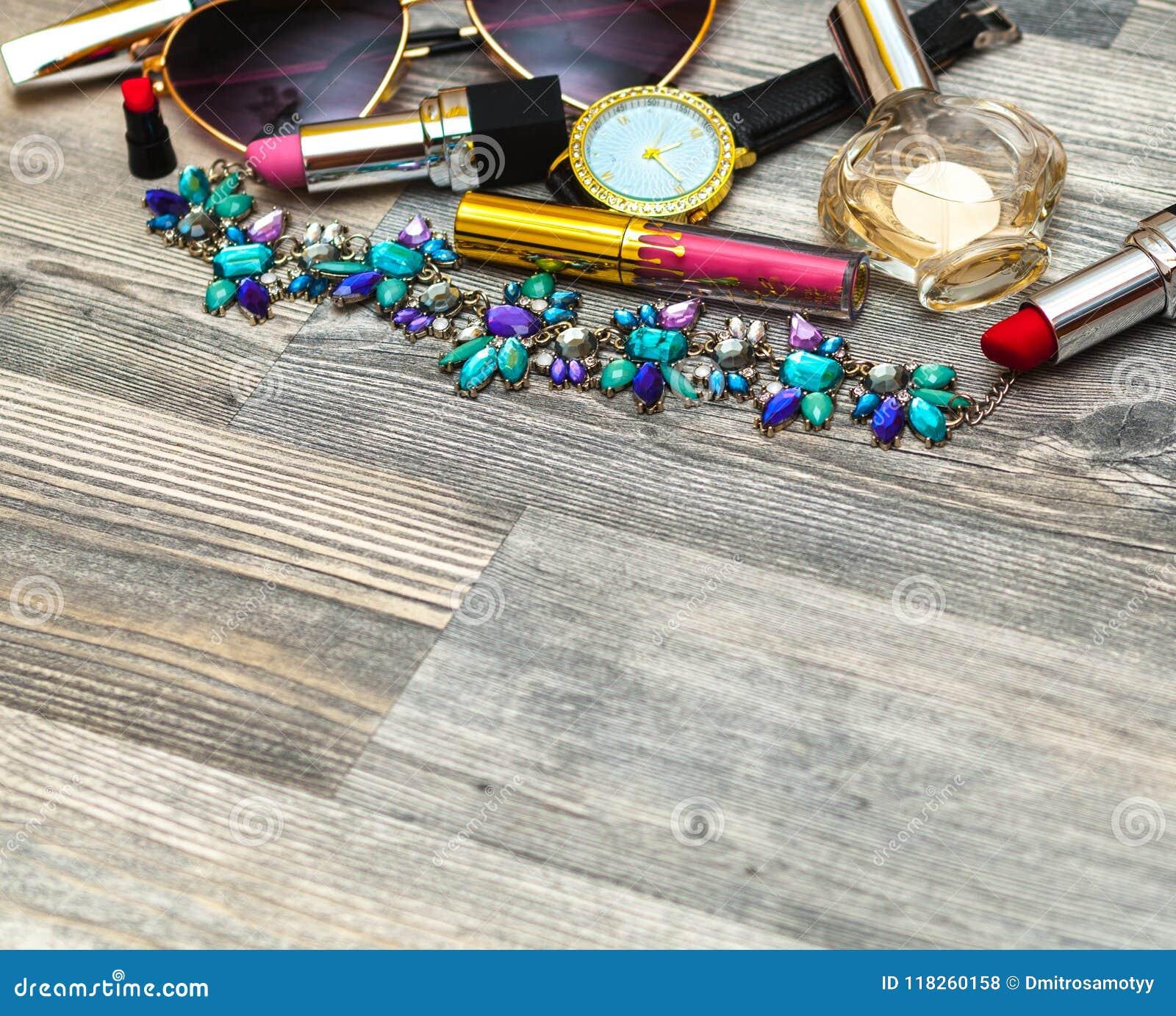 Gestileerde vrouwelijke flatlay met glazen, lippenstift, parfum, horloge, tegenhanger, gestreept overhemd en spot omhoog op witte