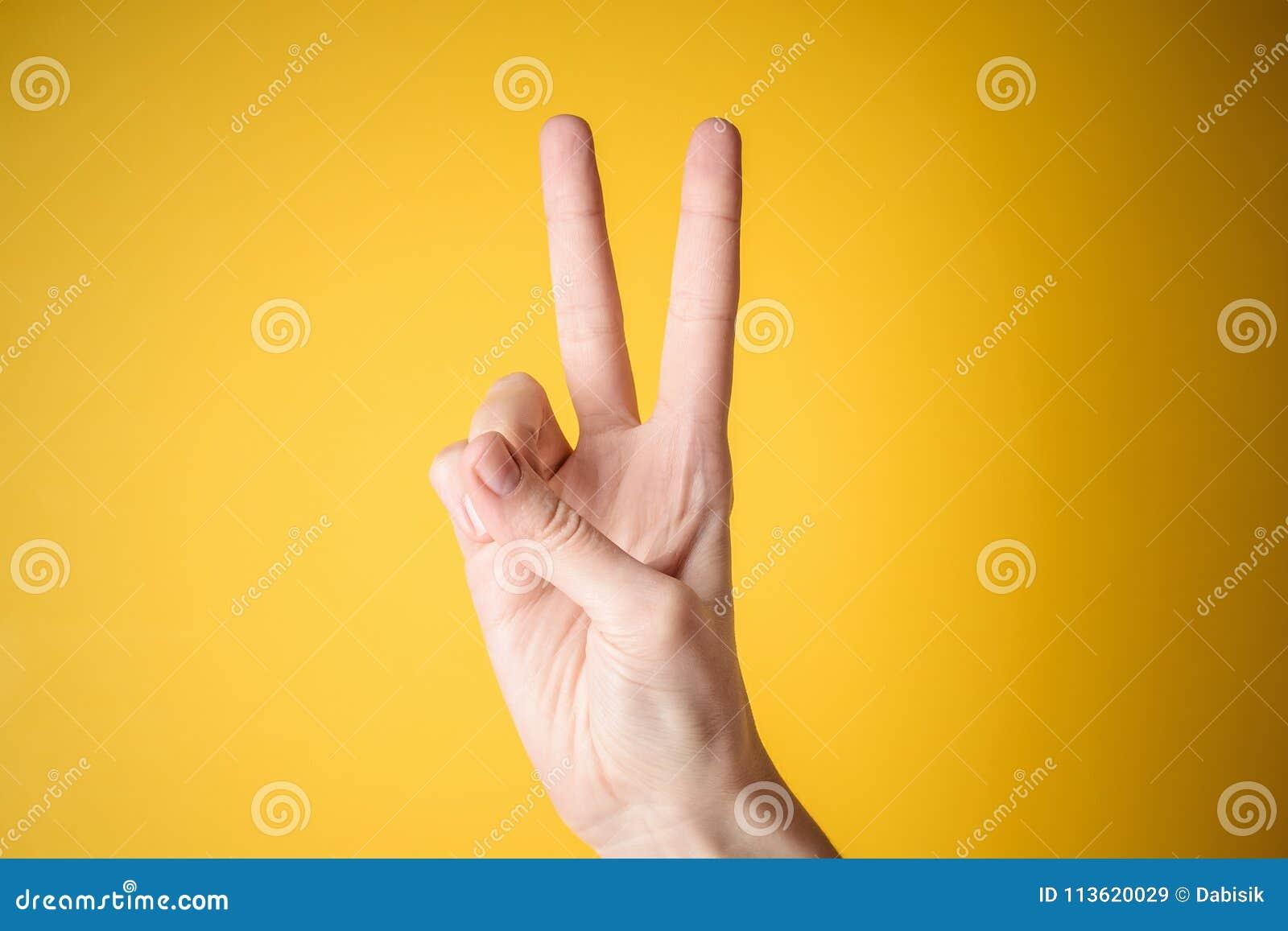 Gesto de la victoria de la mano de la mujer