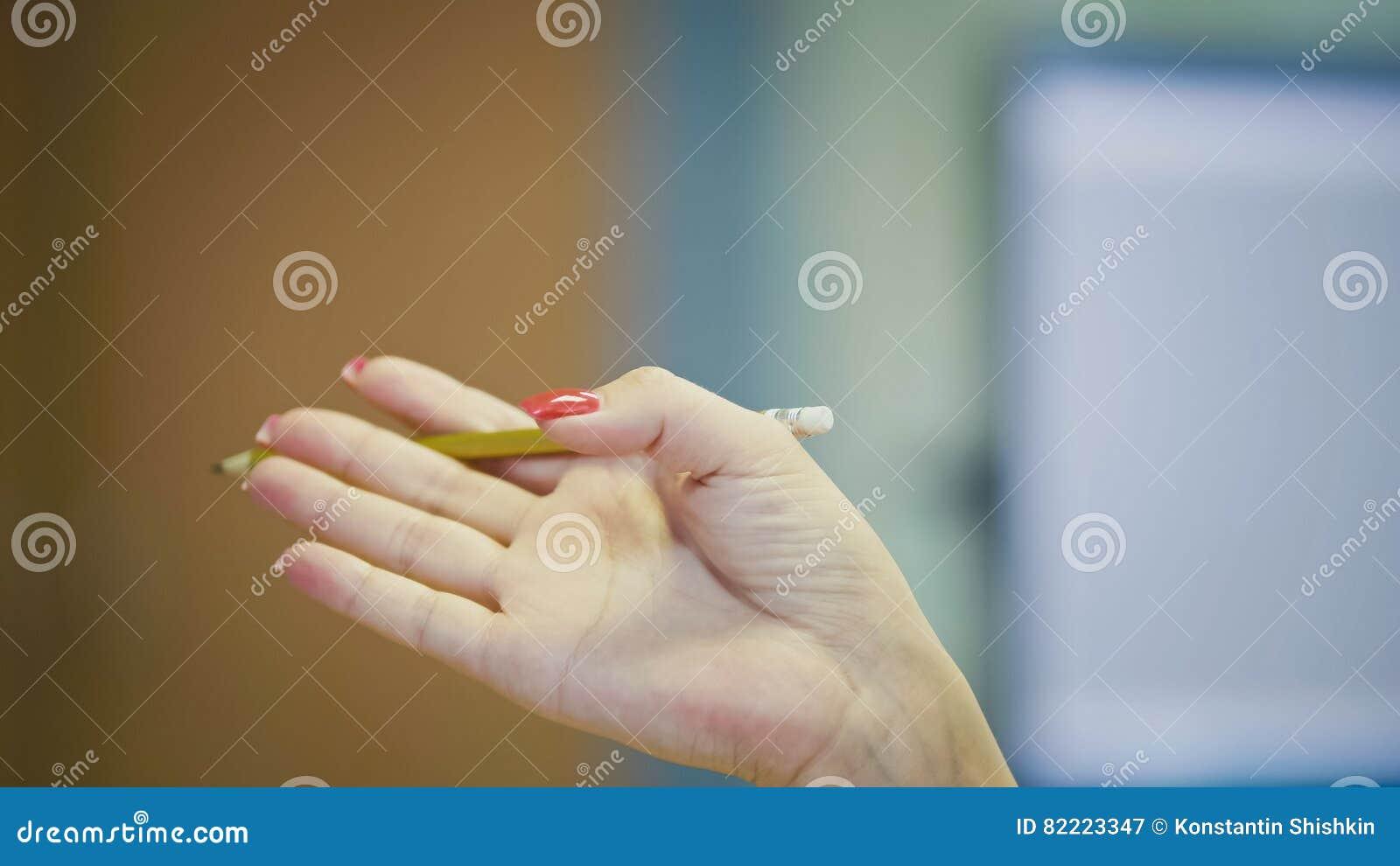 Gestos de mão do gestor de escritório da mulher ao falar no telefone - tratamento de mãos com os pregos vermelhos brilhantes, fim