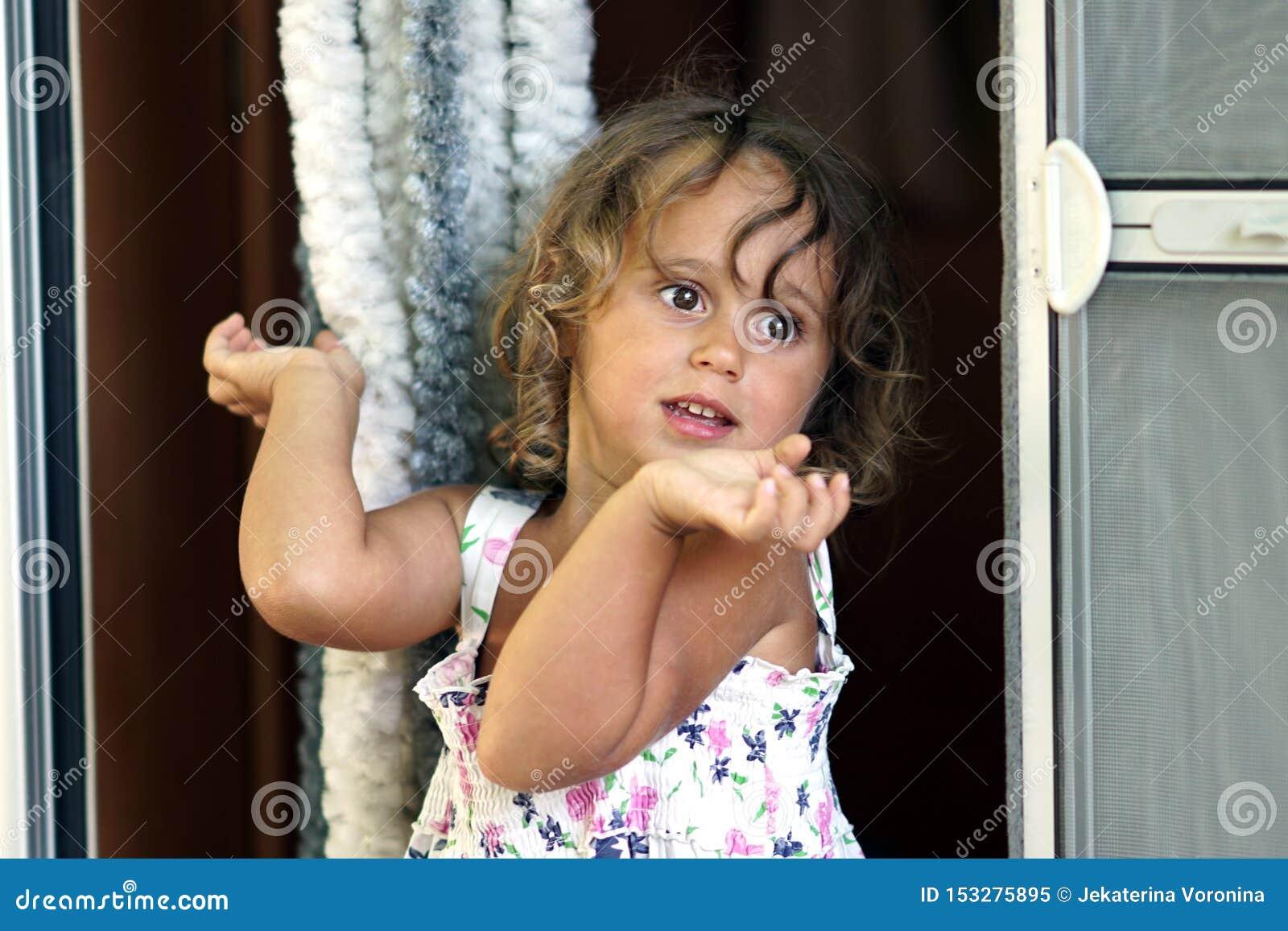Gestos louros de três anos de uma menina com suas mãos