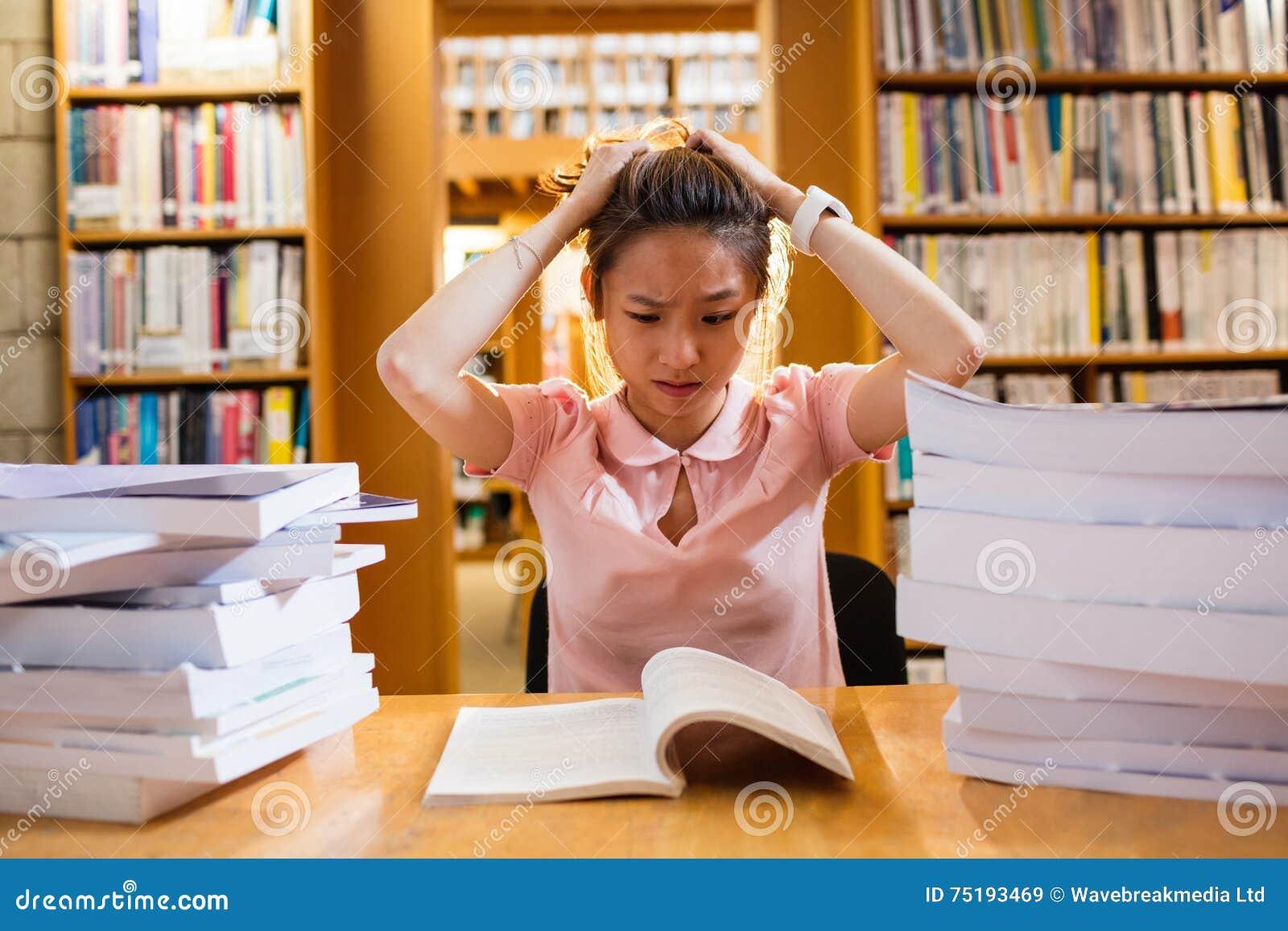 Gestraffte junge Frau, die in der Bibliothek studiert