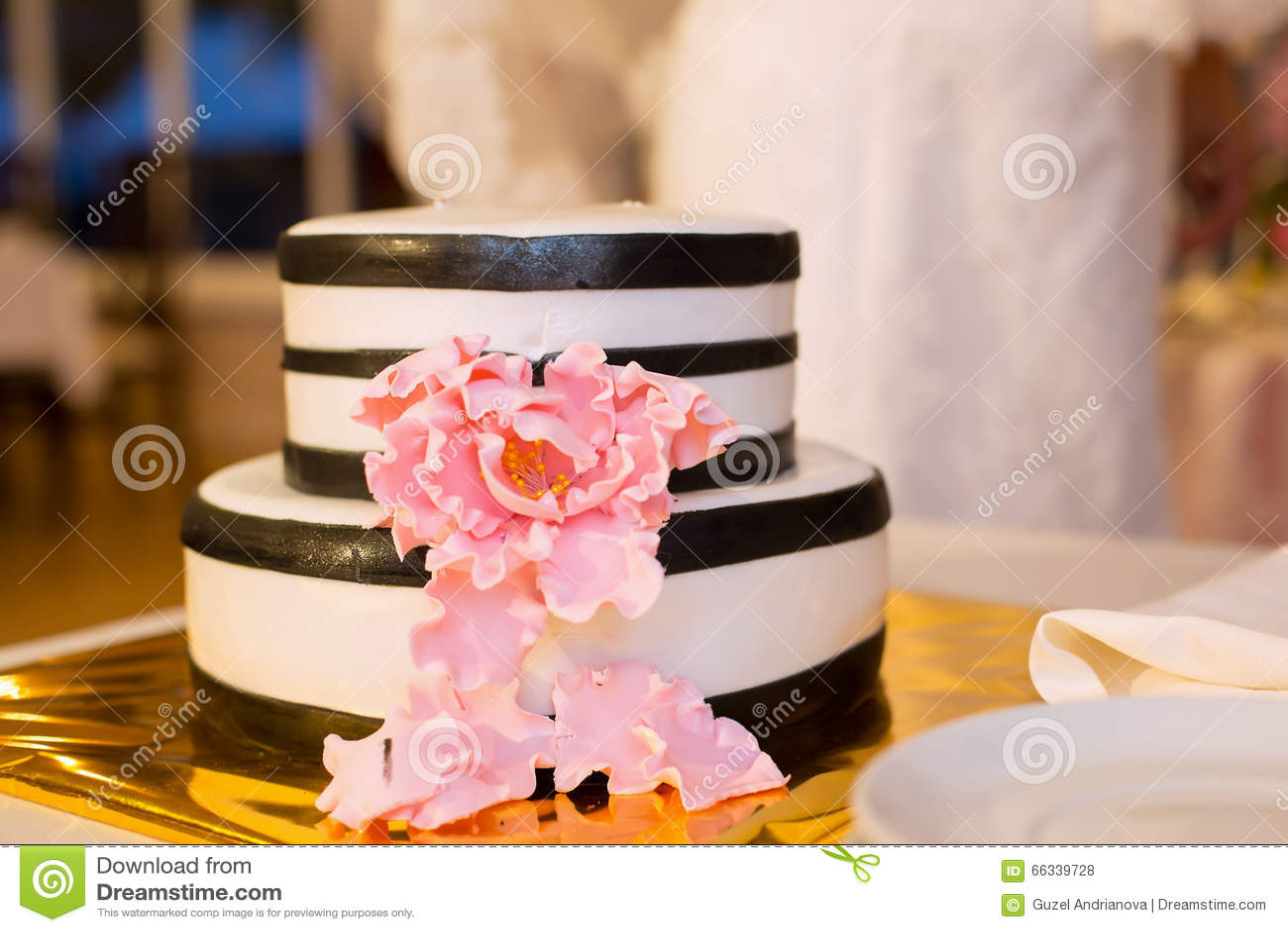 Gestreifte Hochzeitstorte und rosa Blume