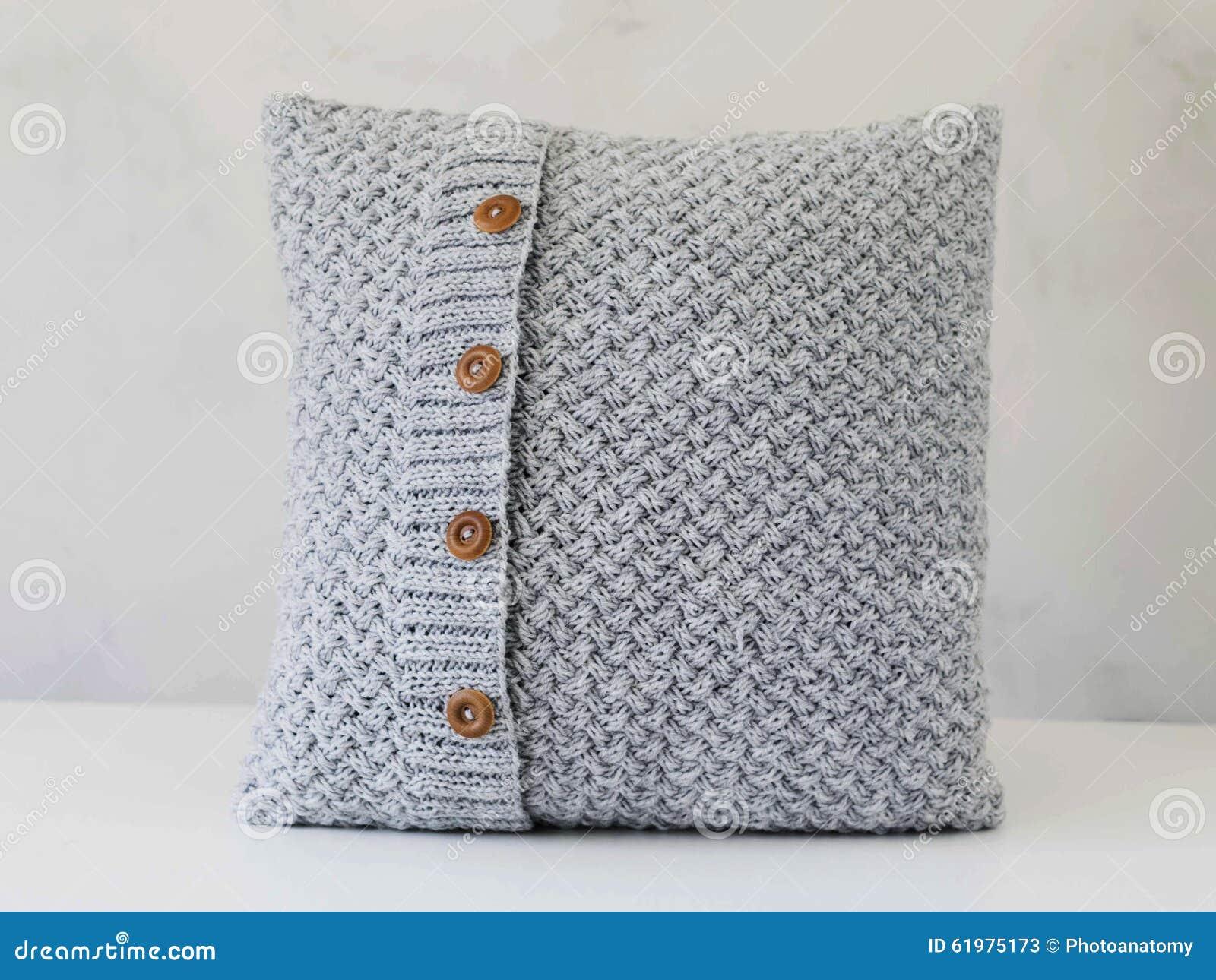 gestricktes graues kissen mit h lzernen kn pfen stockbild bild von kissen cozy 61975173. Black Bedroom Furniture Sets. Home Design Ideas