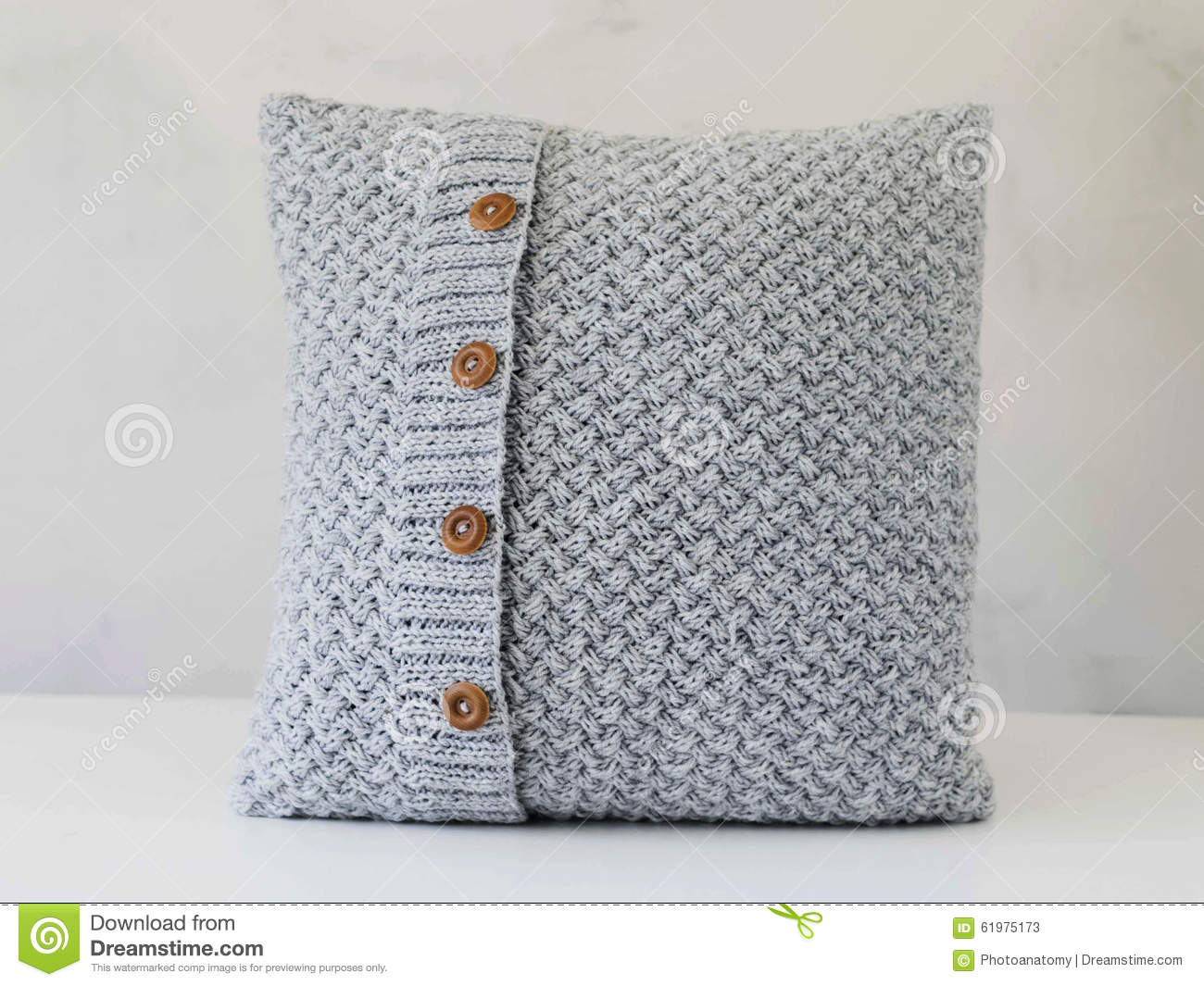 gestricktes graues kissen mit h lzernen kn pfen stockfoto. Black Bedroom Furniture Sets. Home Design Ideas