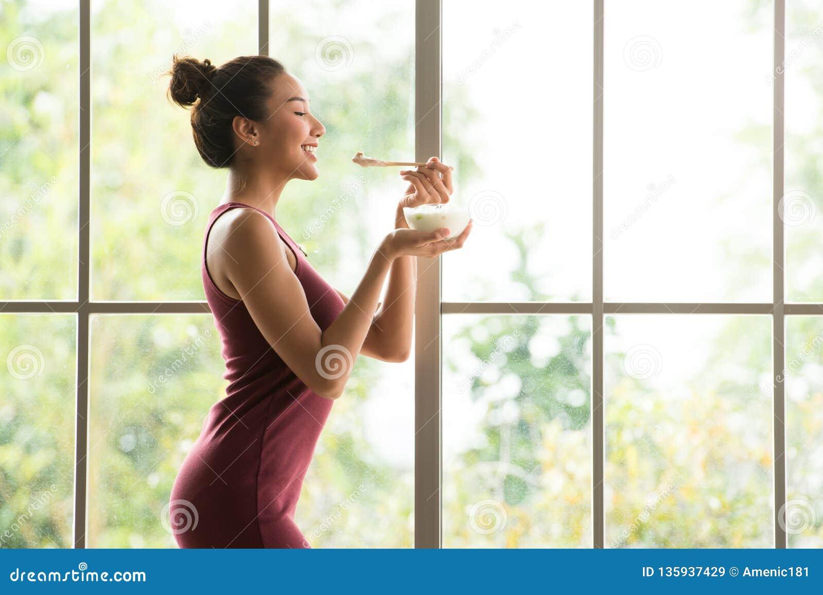 Gesunde Asiatinstellung und Halten einer Schüssel Joghurts schauend entspannt und bequem