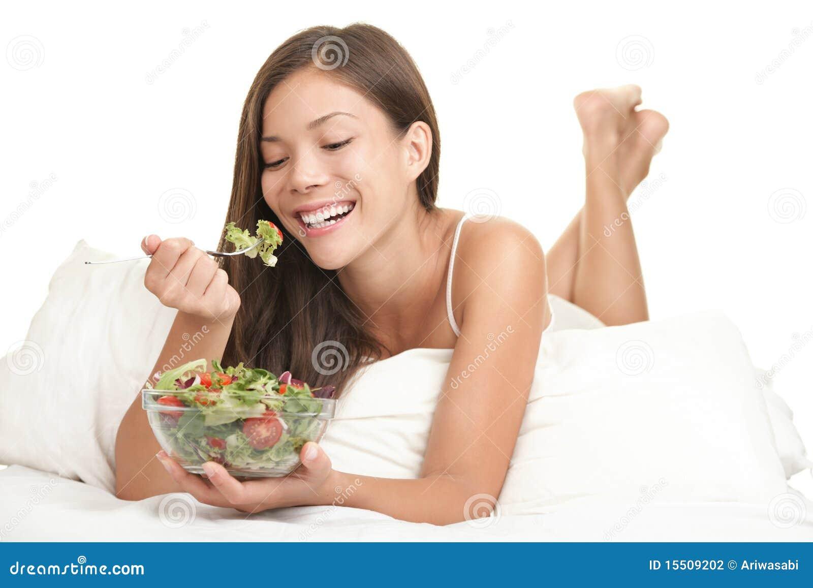 Gesunde Frau, die Salat im Bett isst