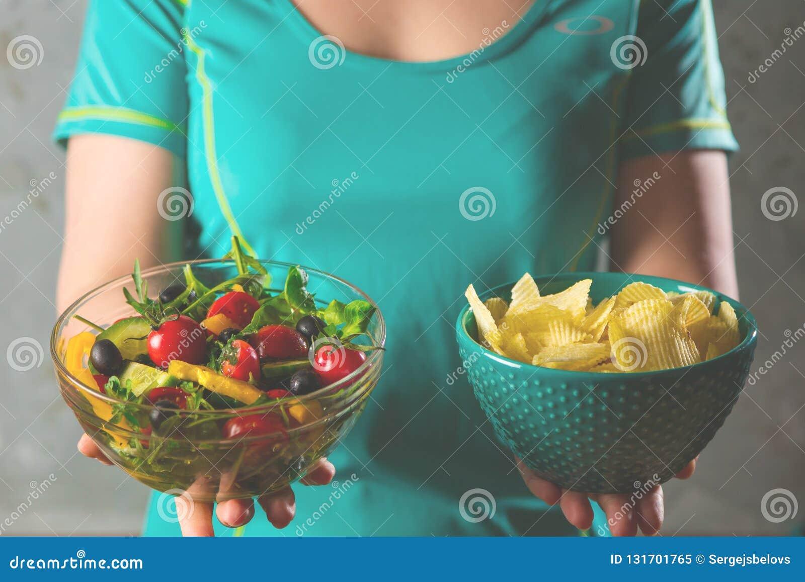 Gesunde junge Frau, die gesunde und ungesunde Nahrung, versuchend, die rechte Wahl zu treffen betrachtet