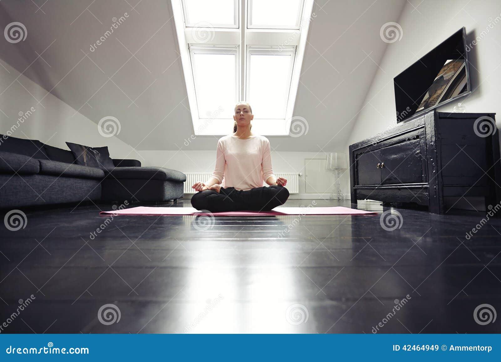 Gesunde junge Frau, die zu Hause meditiert
