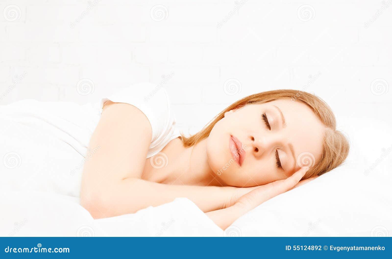 Gesunde junge Schönheit, die im weißen Bett schläft