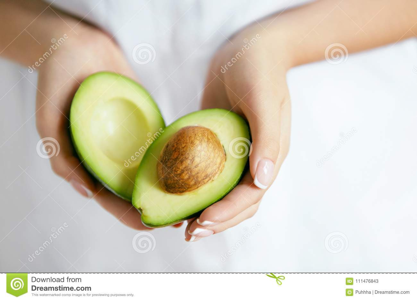 Gesunde Nahrung Avocado in den Frauen-Händen