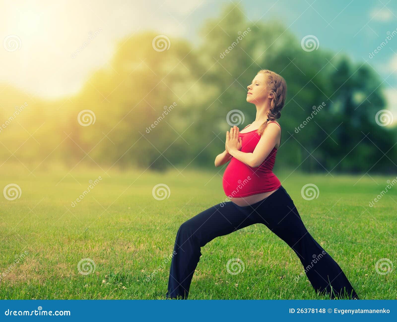 Gesunde schwangere Frau, die Yoga in der Natur tut