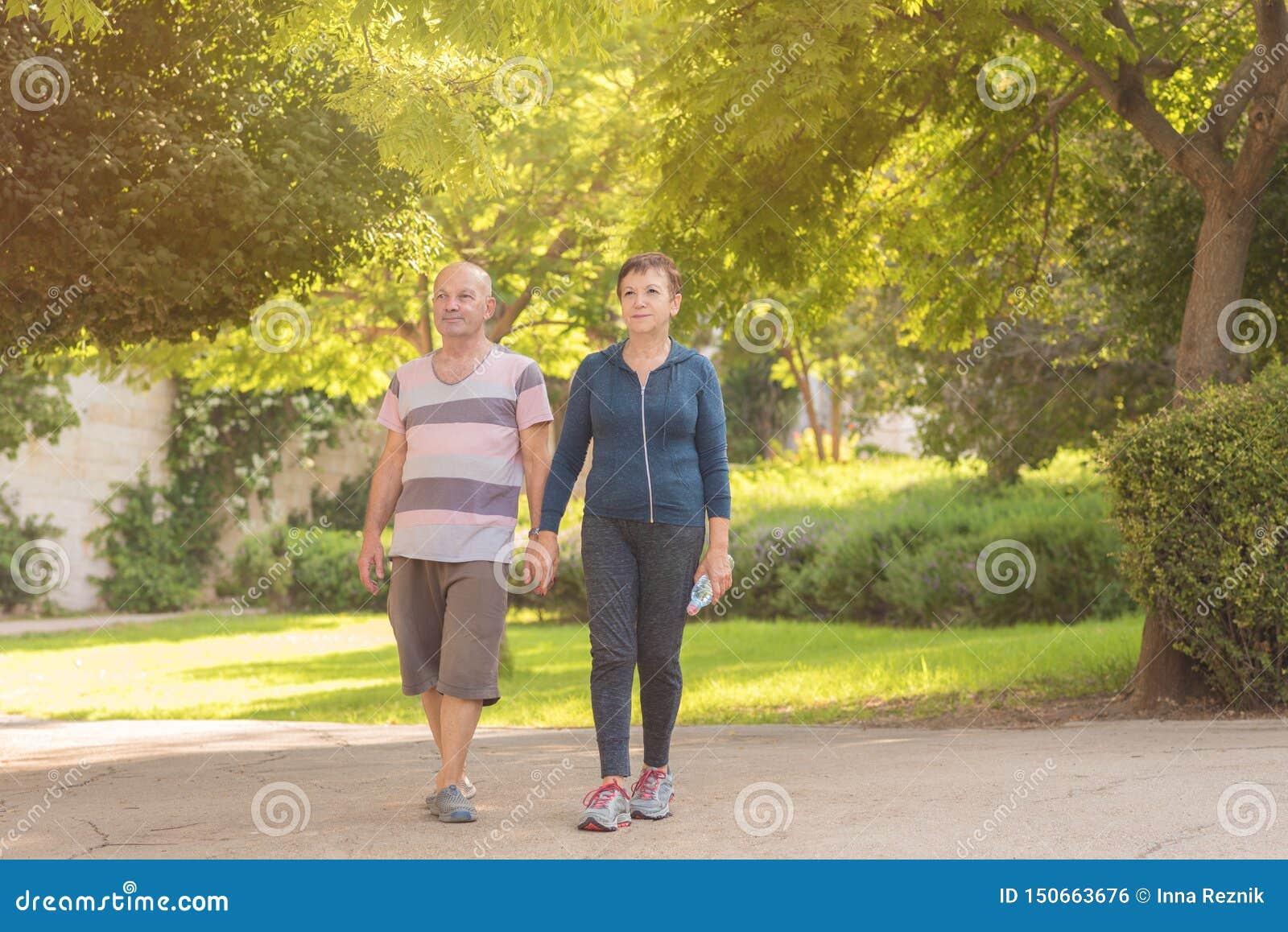 Gesunden und der Leute Konzept der Familie, des Alters, des Sports, - glückliches älteres Paarhändchenhalten und zusammen trainie