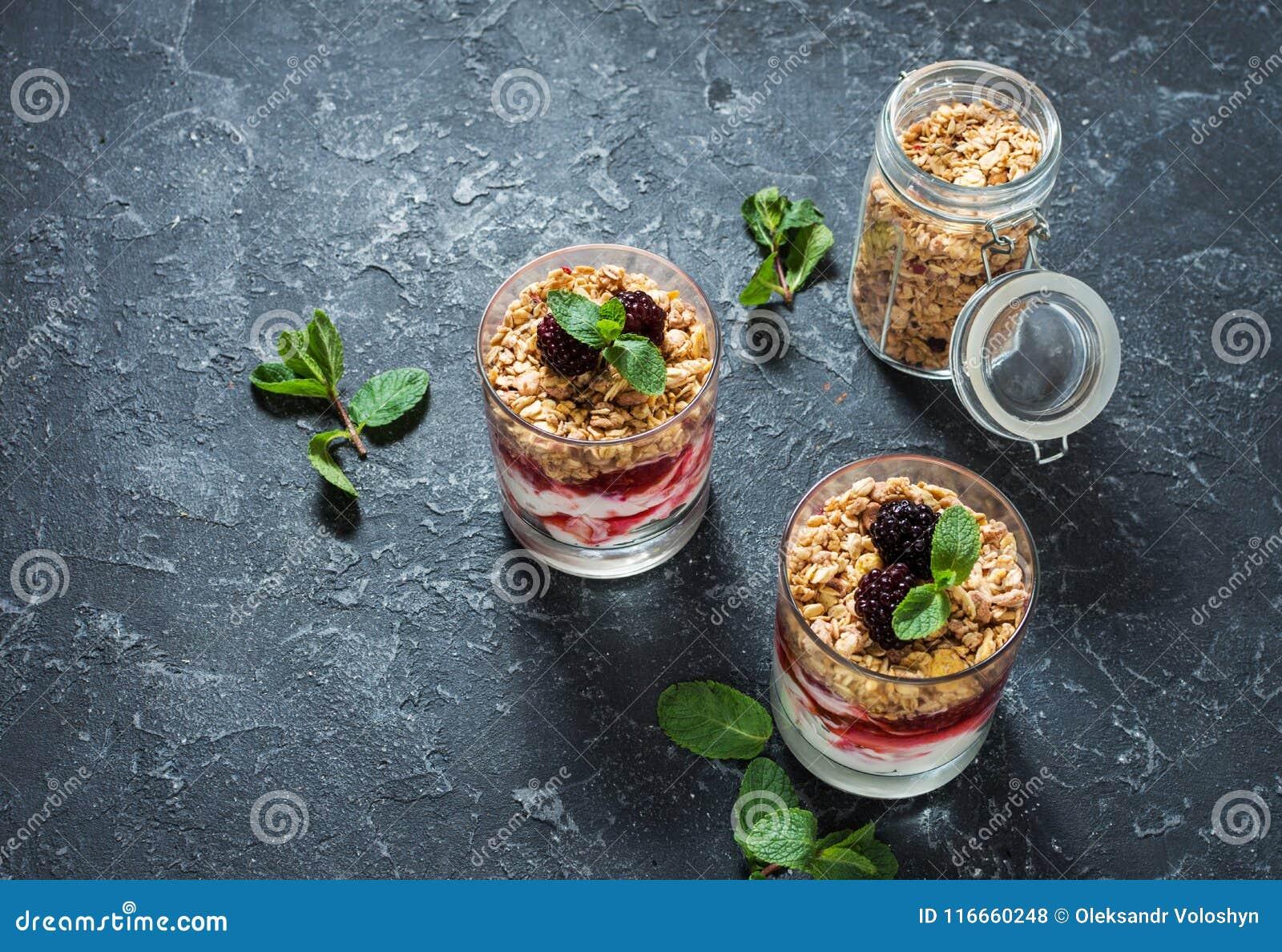 Gesunder überlagerter Nachtisch mit Jogurt, Granola, Stau, Brombeere im Glas auf Steinhintergrund