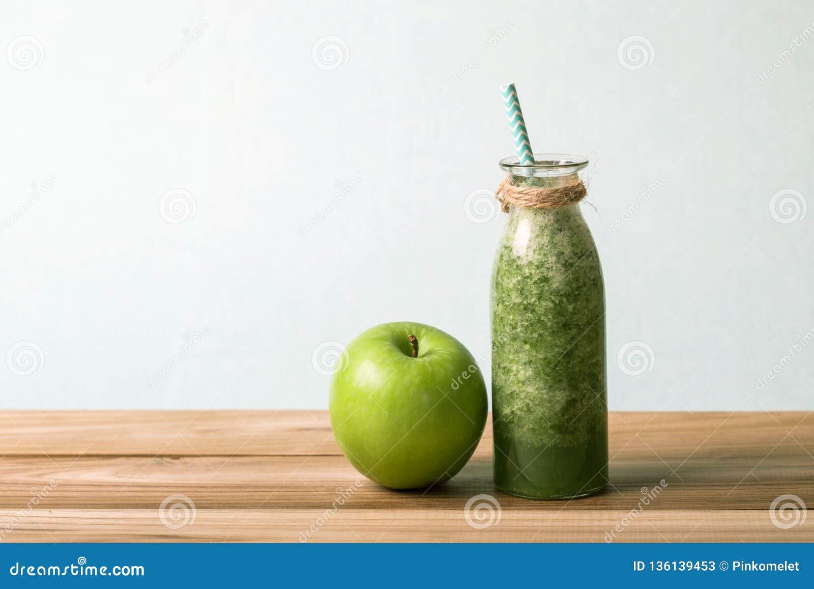 Gesunder frischer grüner Smoothiesaft in der Glasflasche auf Holztisch für gesundes Detox- und Diätgewohnheitskonzept