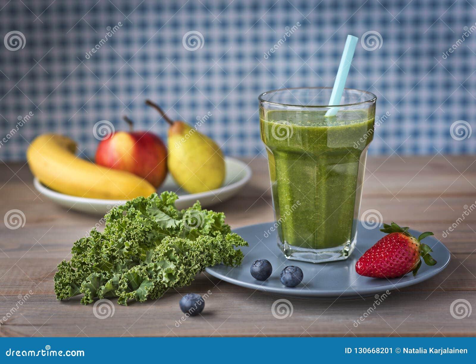 Gesunder grüner Smoothie mit Kohl, Erdbeeren, Blaubeeren, Banane, Apfel, Birne und Honig in einem Glas gegen ein rustikales hölze