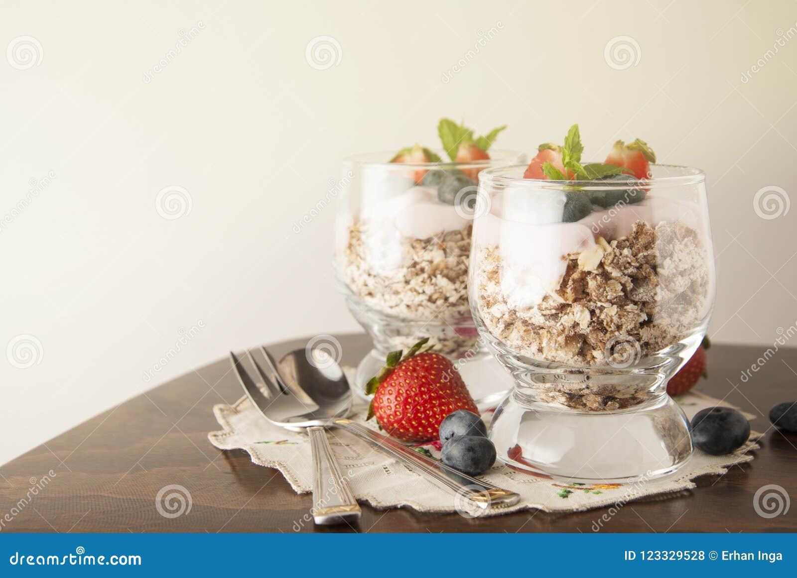Gesundes Frühstück, Hafermahlzeit mit Früchten: bluebery, strawbery und Minute, Parfait in zwei Gläsern auf einem rustikalen Hint
