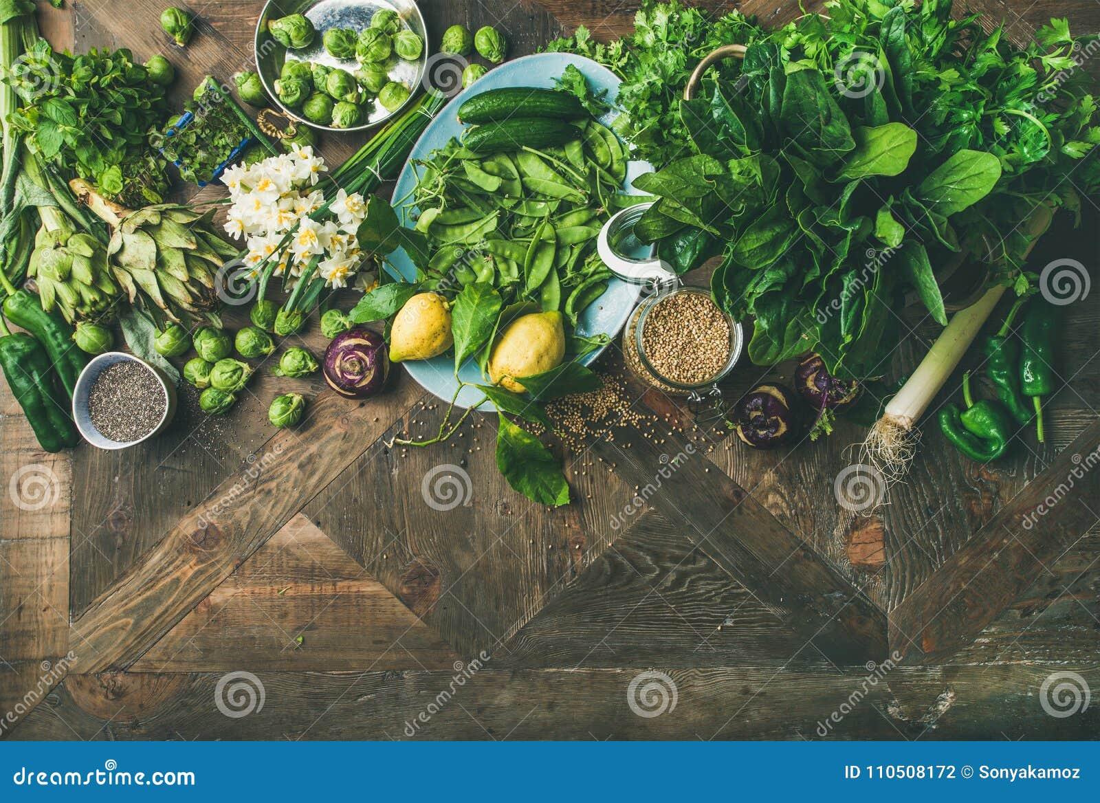 Gesundes Lebensmittel des strengen Vegetariers des Frühlinges, das Bestandteile über hölzernem Hintergrund kocht