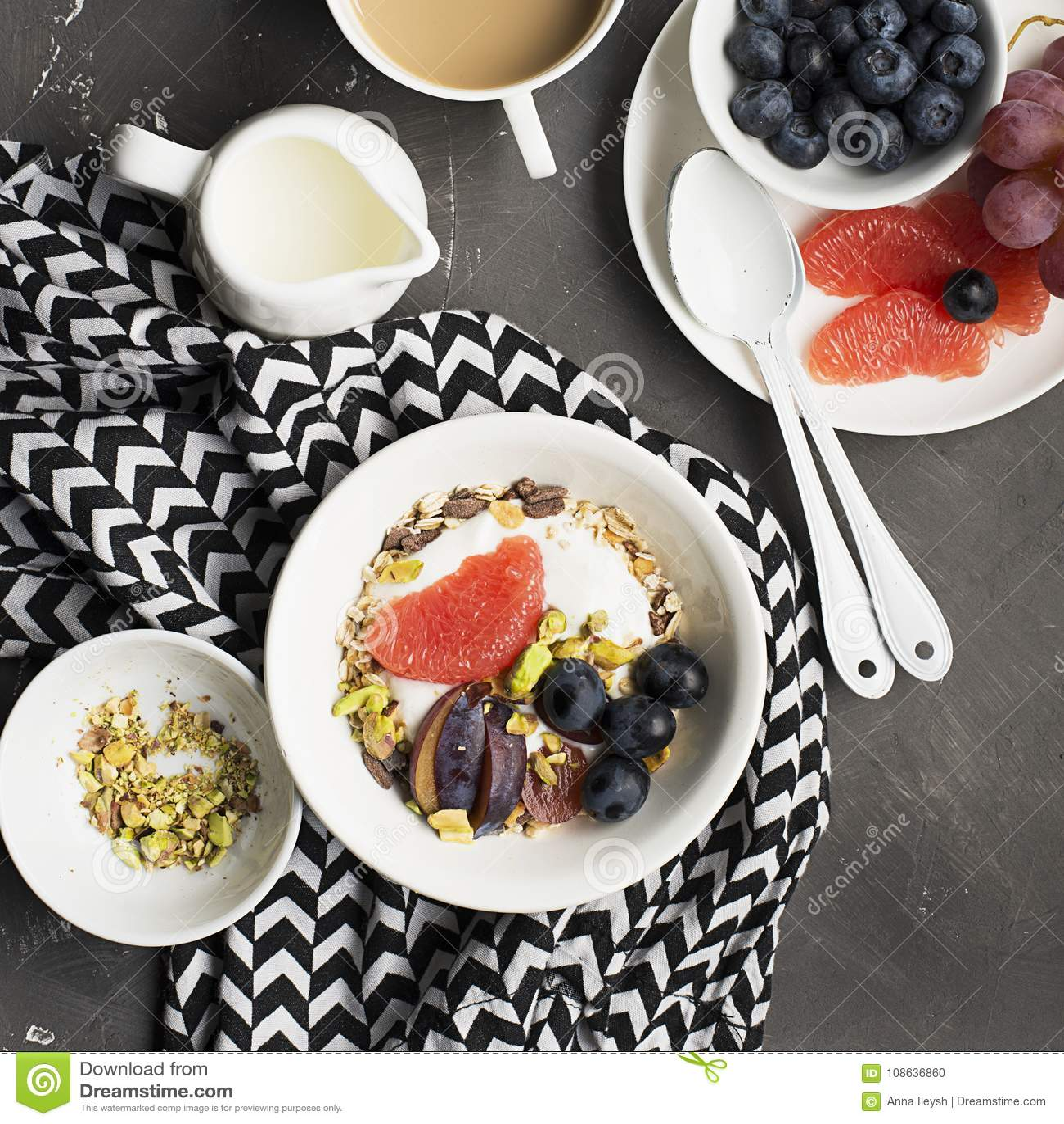 Gesundes saisonalfrühstück: Jogurt, Schokoladengranola, rosa Pampelmuse, Trauben, Pistazien Beschneidungspfad eingeschlossen Kopi