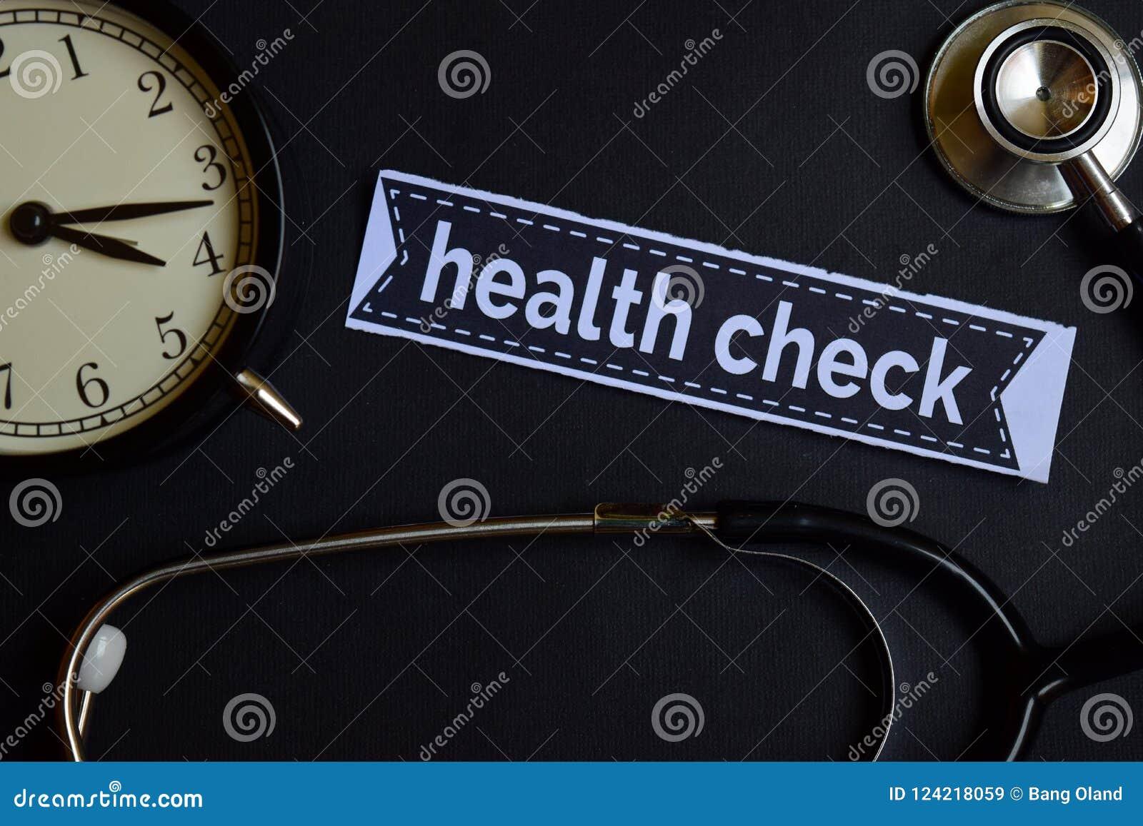 Gesundheits-Check auf dem Druckpapier mit Gesundheitswesen-Konzept-Inspiration Wecker, schwarzes Stethoskop