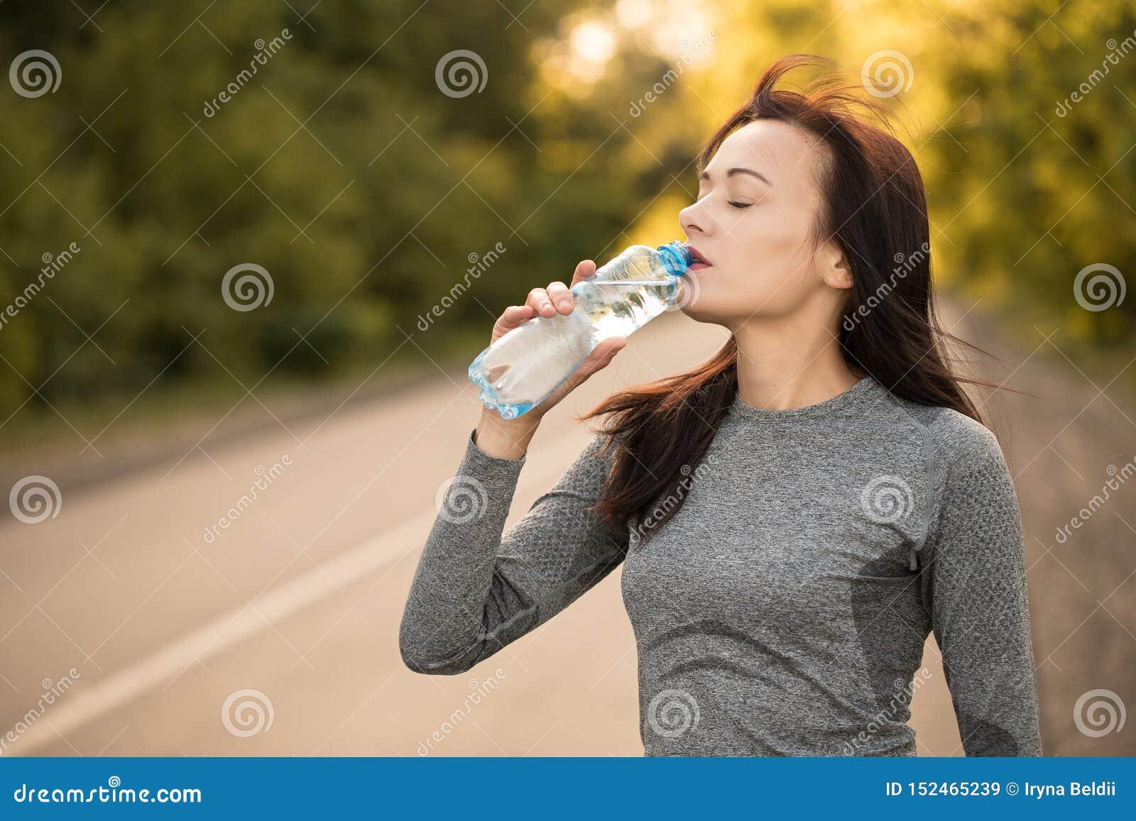 Getränkwasser während der Übung Laufendes Bild des M?dchens/der Frau, das verwendet werden k?nnte, um Produkte und Dienstleistung
