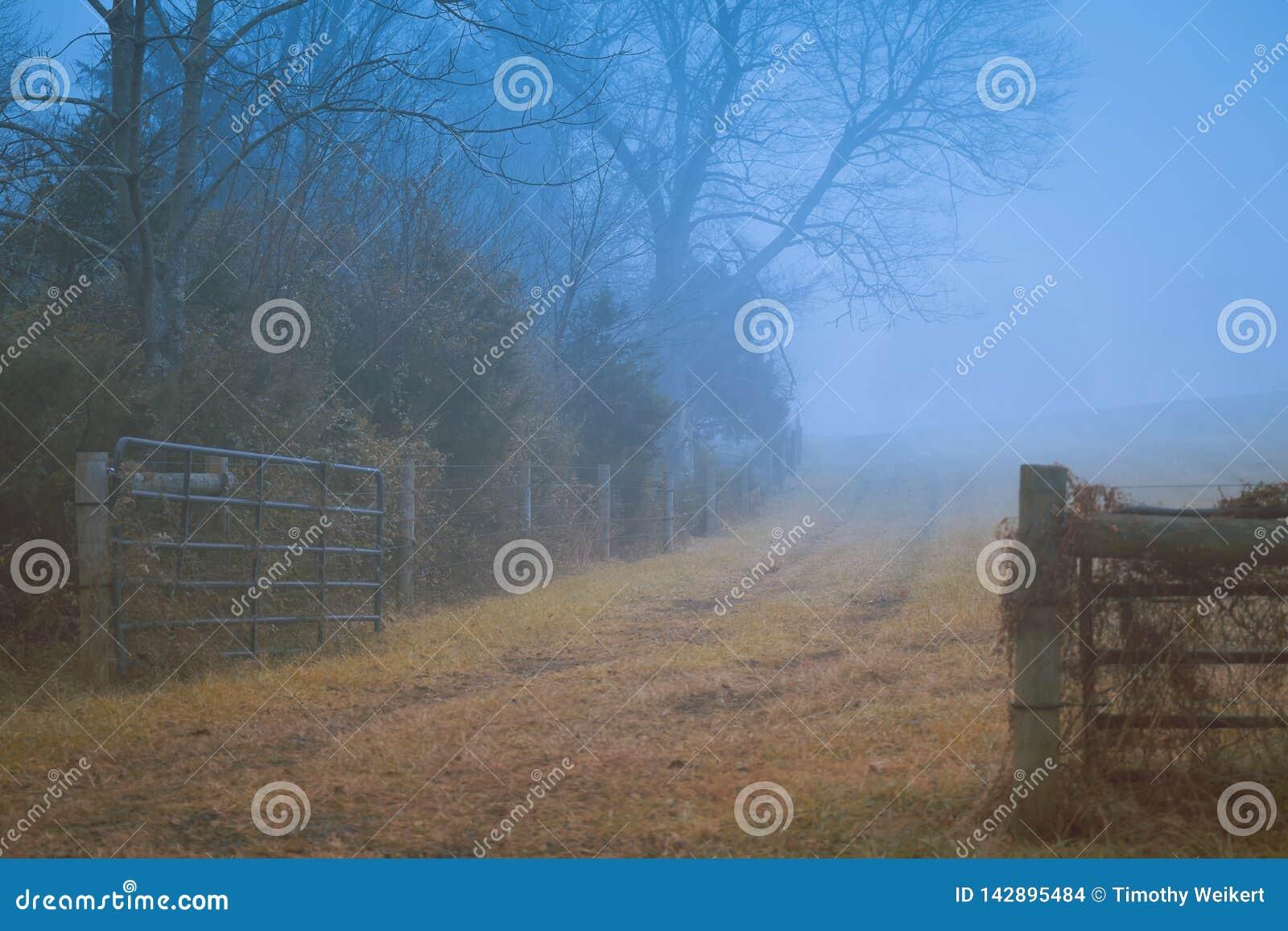 Gettysburg, PA/EUA - em dezembro de 2018: Uma cerca de madeira velha ao longo da estrada de terra místico na névoa Conceito do ou