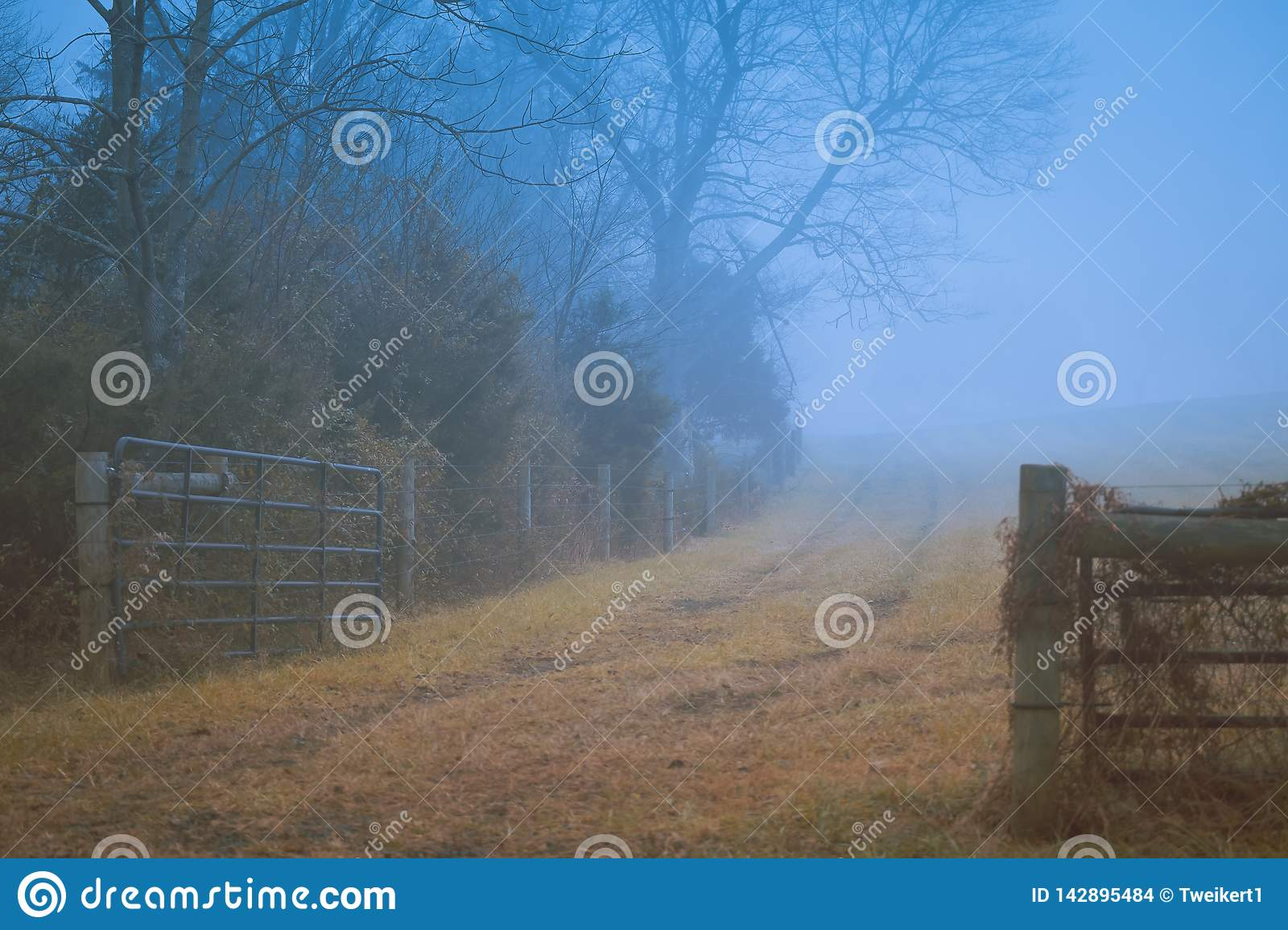 Gettysburg, PA / USA - December, 2018: An old wooden fence along the mystical dirt road in the fog. Autumn concept