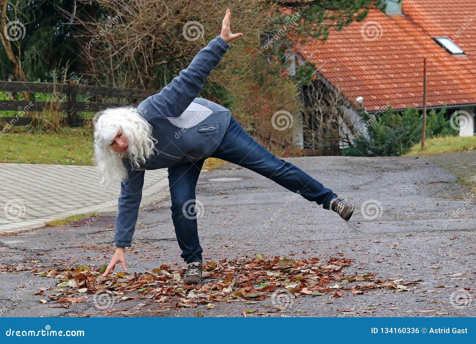 Gevaar in de herfst Een vrouw glijdt op een weg op natte bladeren uit