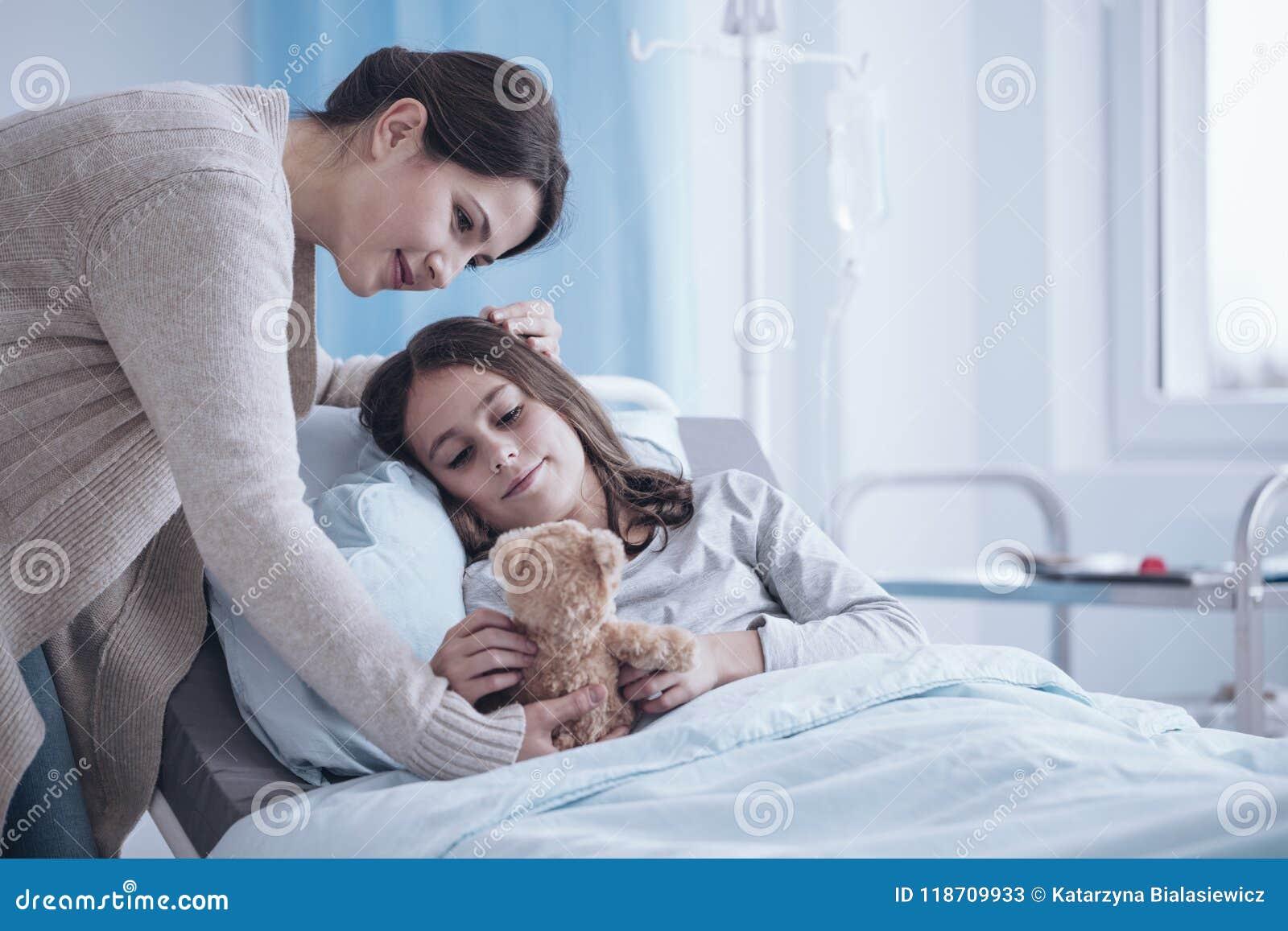 Gevende moeder die een pluchestuk speelgoed geven aan zieke dochter die in liggen hos